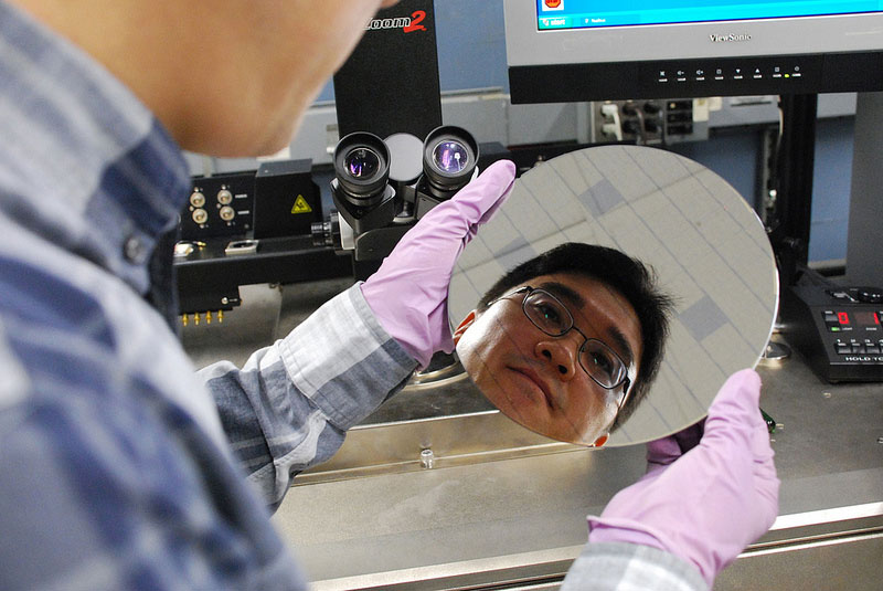 IBM researcher Hongsik Park looks over a chip wafer with carbon nanotubes. The wafer has two surfaces, trenches made of hafnium oxide that attract carbon nanotubes in a special solution silicon oxide that doesn't.