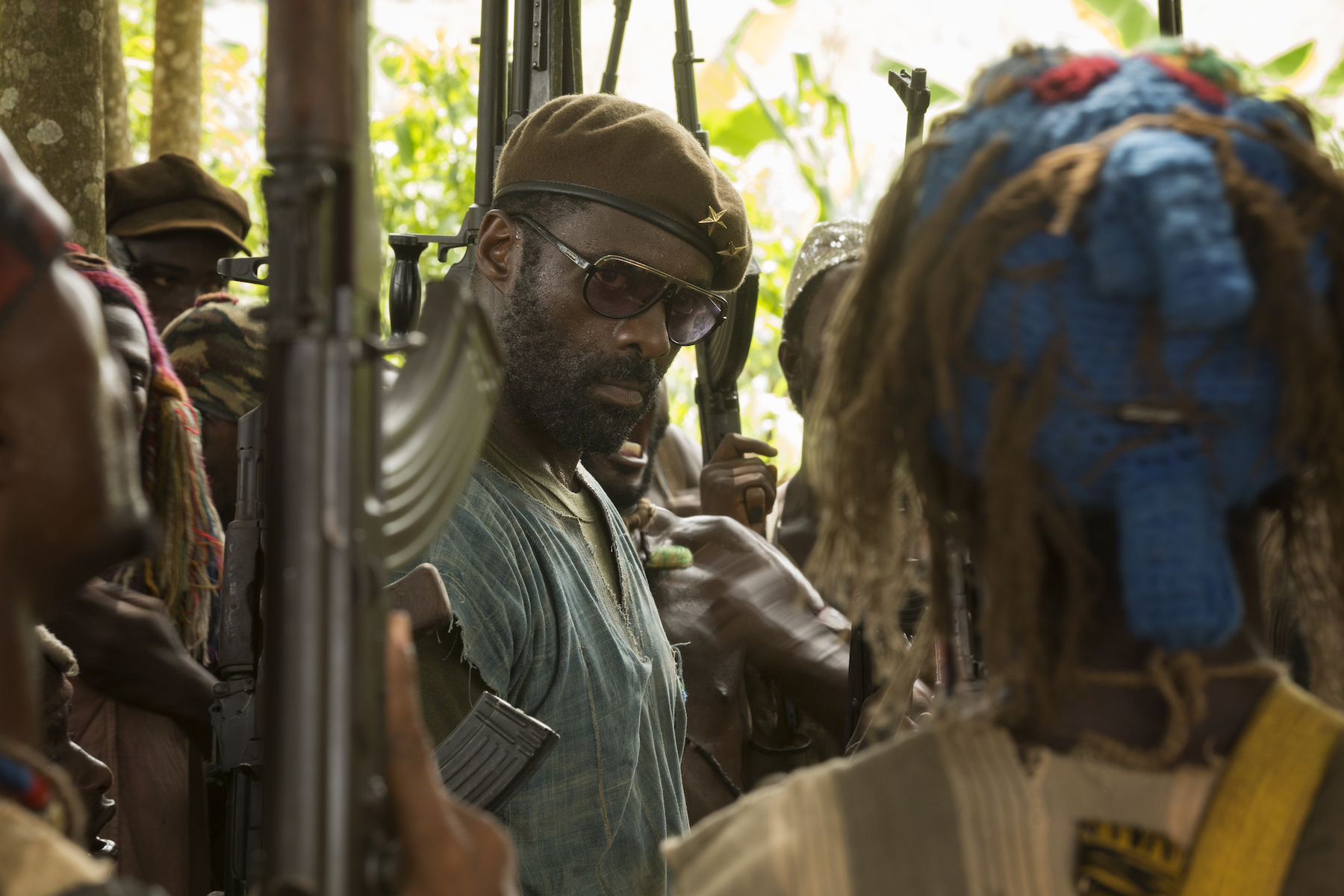 Actor Idris Elba stands as a warlord in a crowd of gun-toting soldiers in Beasts of No Nation