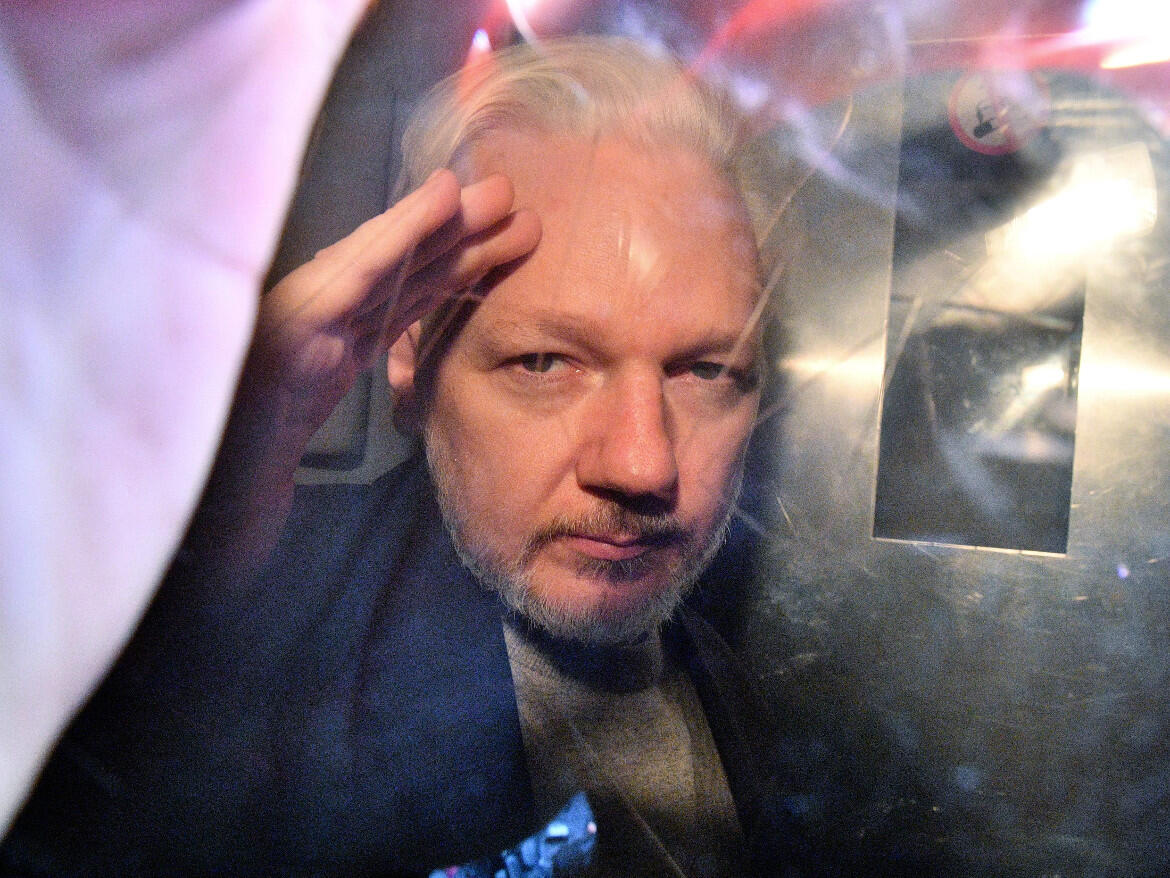 WikiLeaks founder Julian Assange gestures from the window of a prison van as he's driven out of a London court on May 1, 2019, after being sentenced to 50 weeks in prison for breaching his bail conditions in 2012.