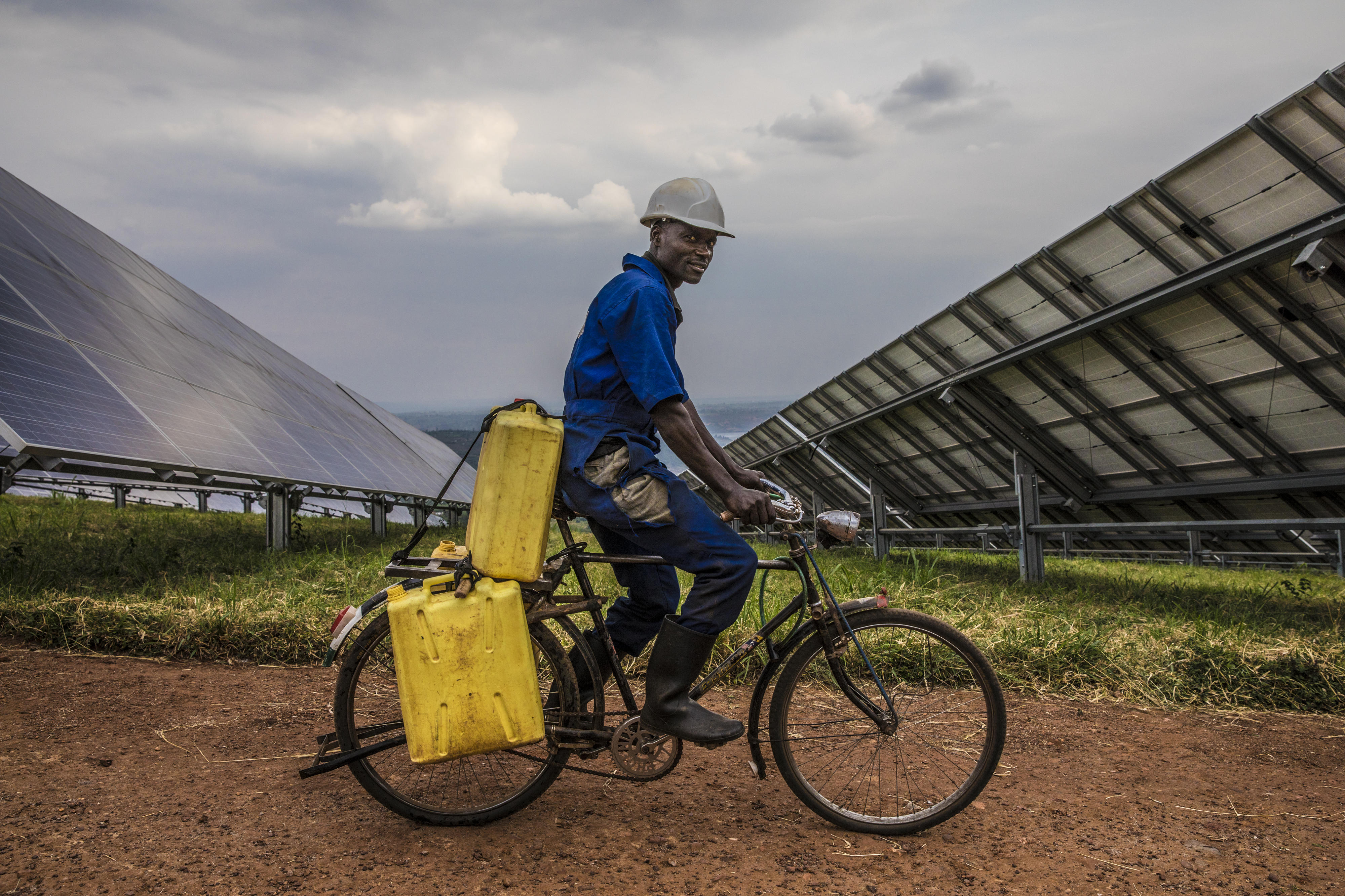 A worker at the Rwamagana Solar Power Station rides through the plant with jugs of water.