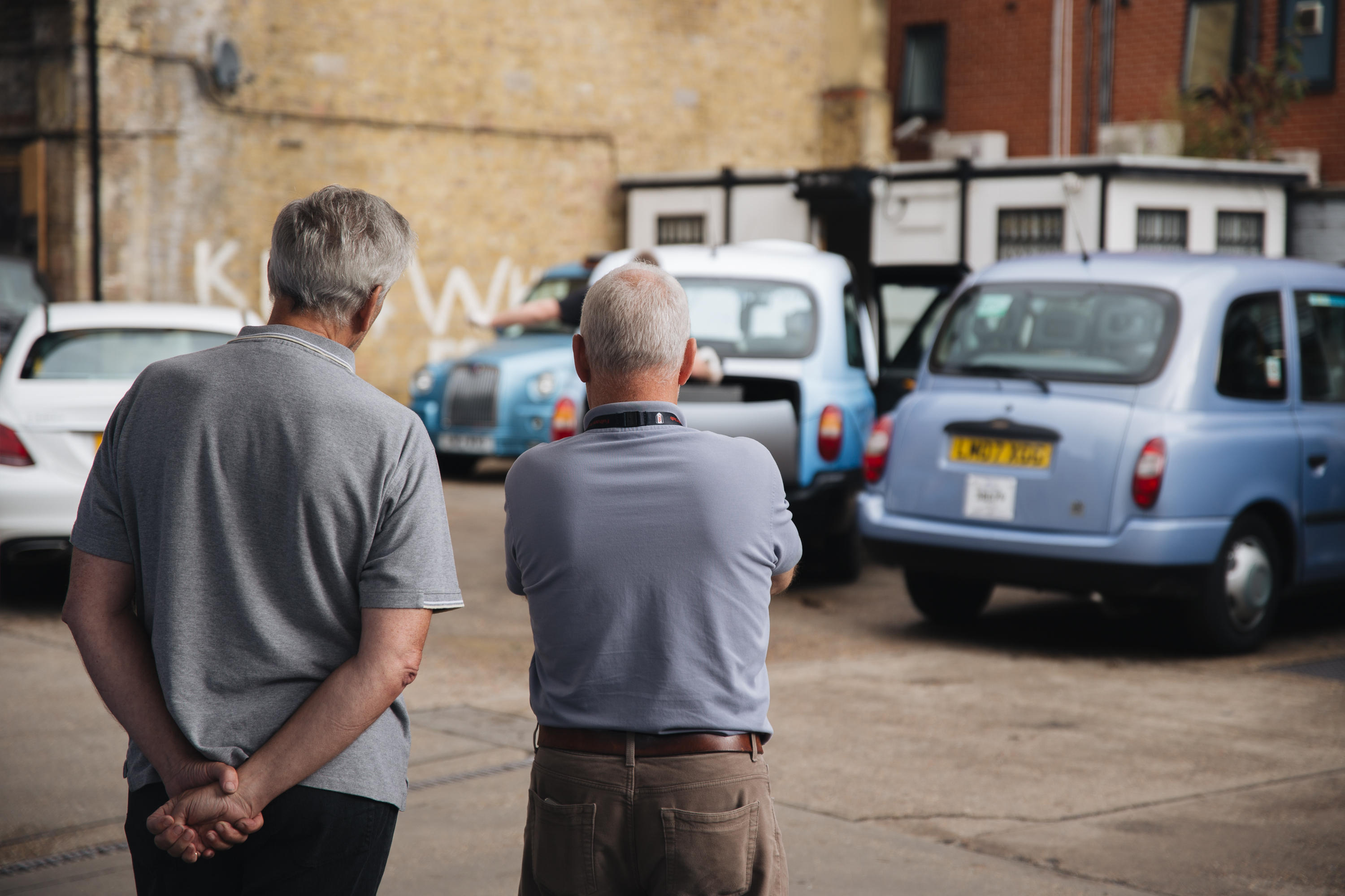 Two taxi drivers take a moment to relax and watch their cars being serviced in the Southwark cab station. The man on the right (who requested not to be named) was waiting to have his payment machines removed, having just finished his last ever trip after 48 years of driving.