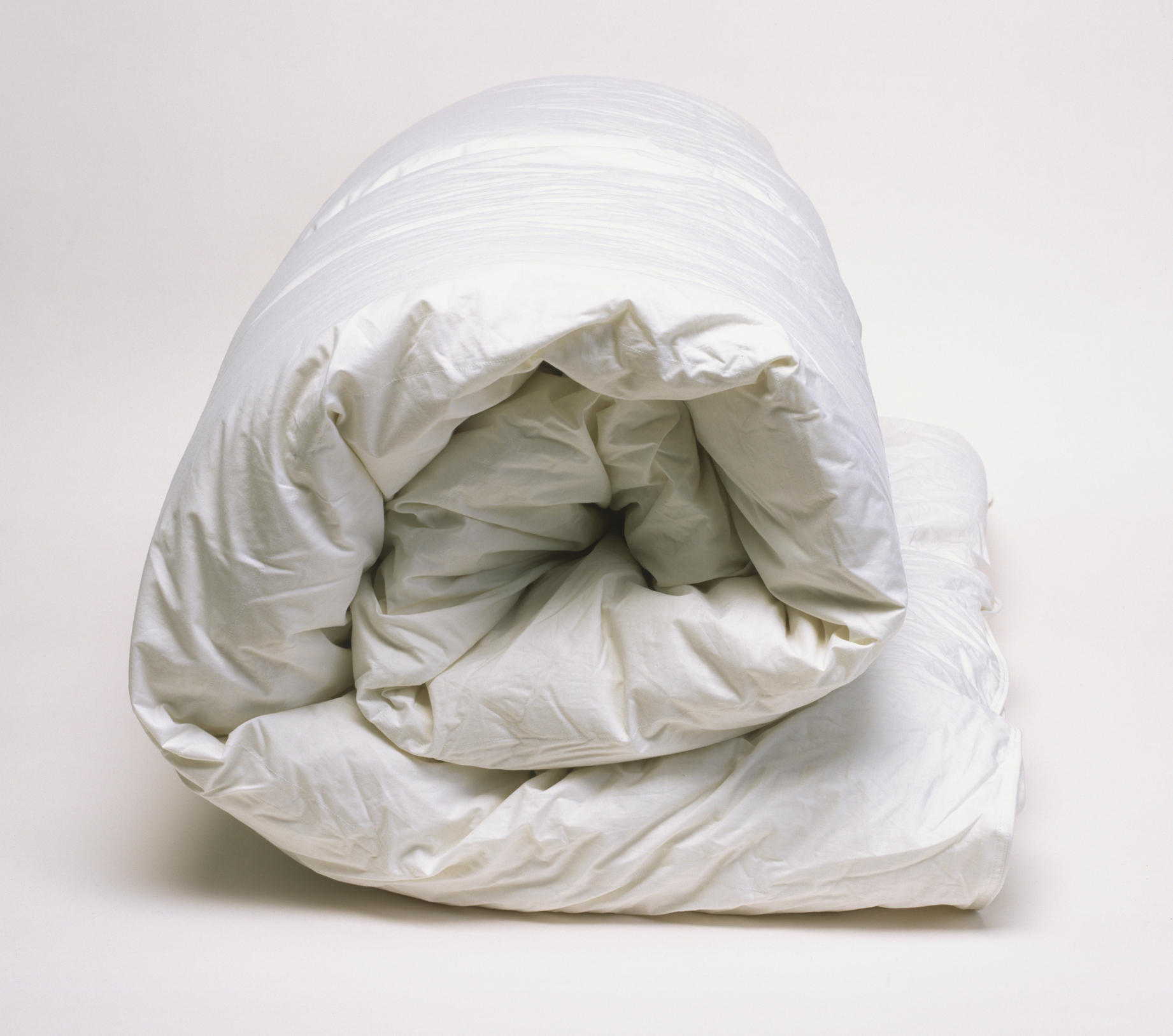 White goose-down duvet, rolled up, side view.