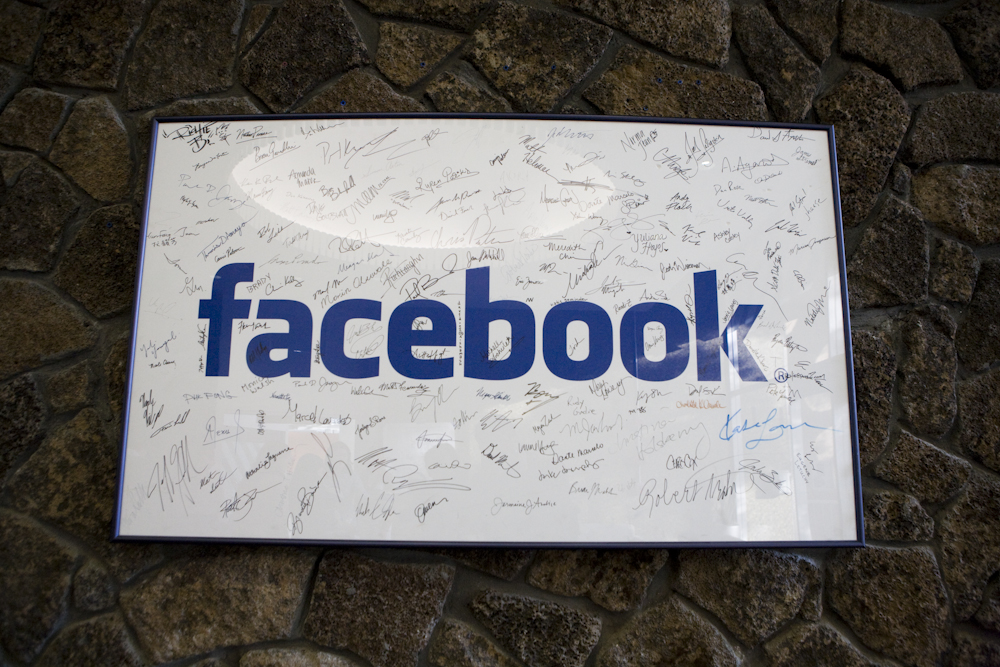 A framed Facebook logo, filled with employees' signatures, hangs in the lobby of the company's Palo Alto, Calif., building in June 2009.