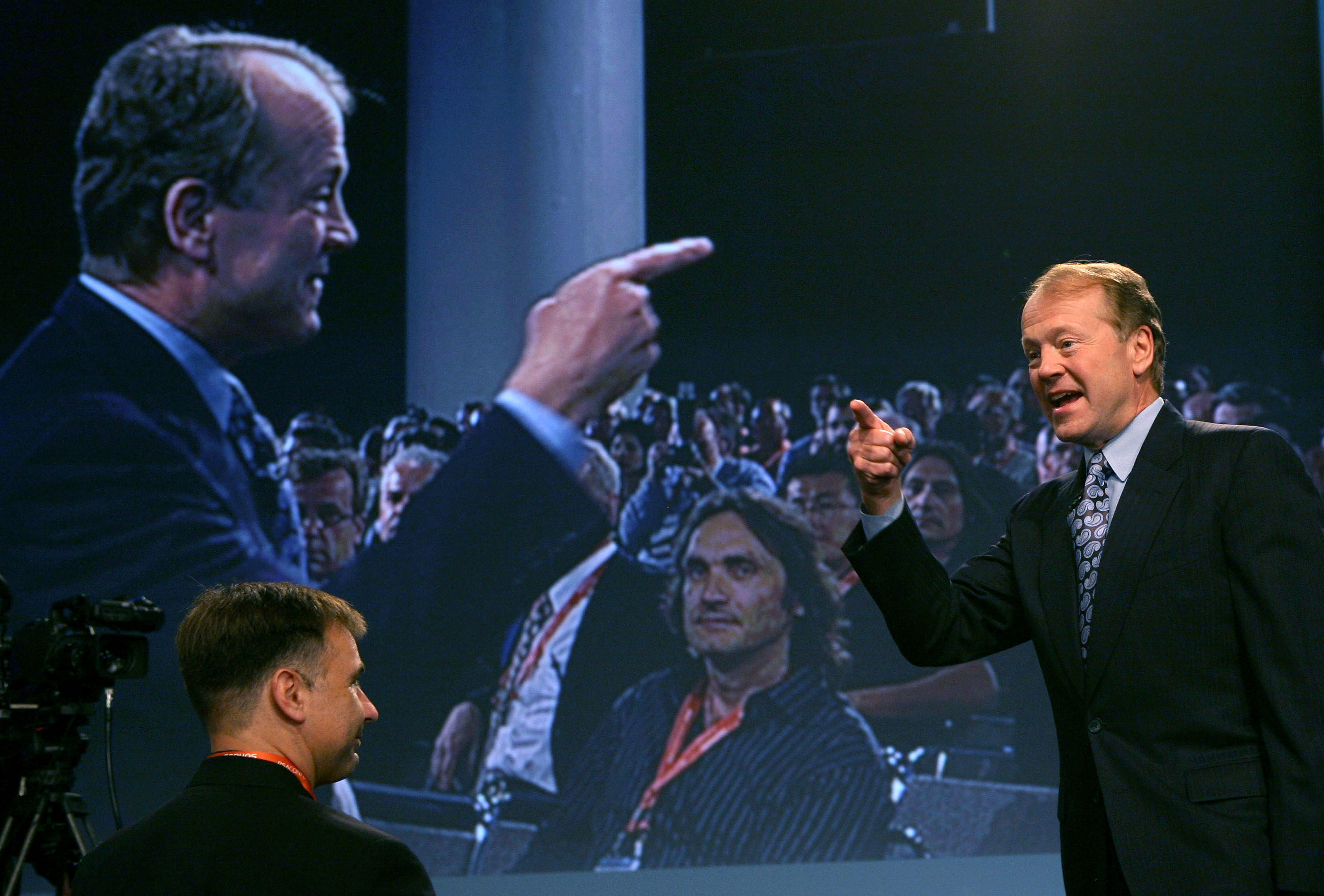 Cisco Chairman and CEO John Chambers delivers a keynote address during the RSA Conference in 2009. Chambers stands to the right, pointing. Behind him, a video screen shows his mirror image pointing back at him. This year, 19 out of 20 keynote speakers will be men.