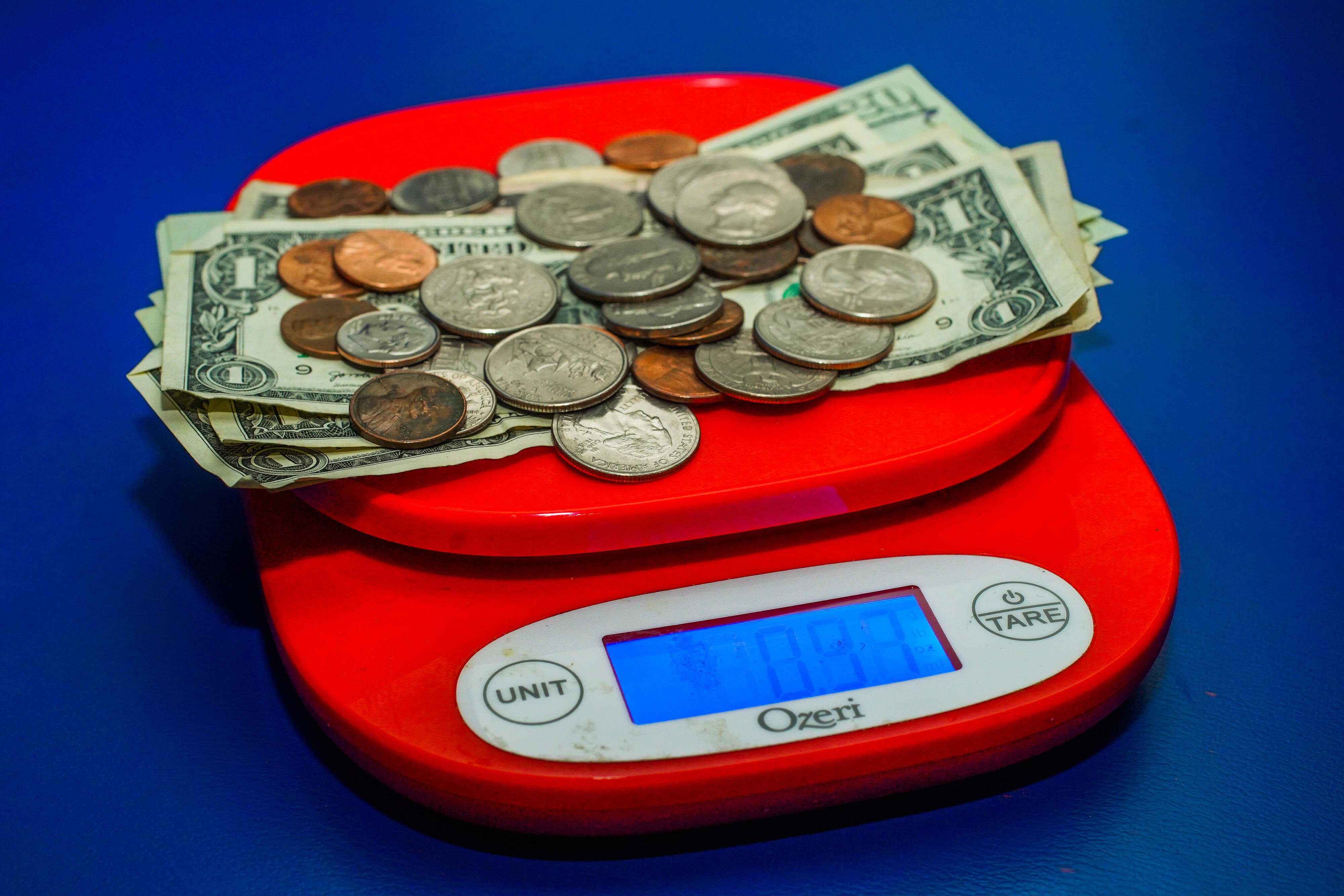 010-stimulus-piggy-bank-tear-falling-money-clip-weighing-cash-scale