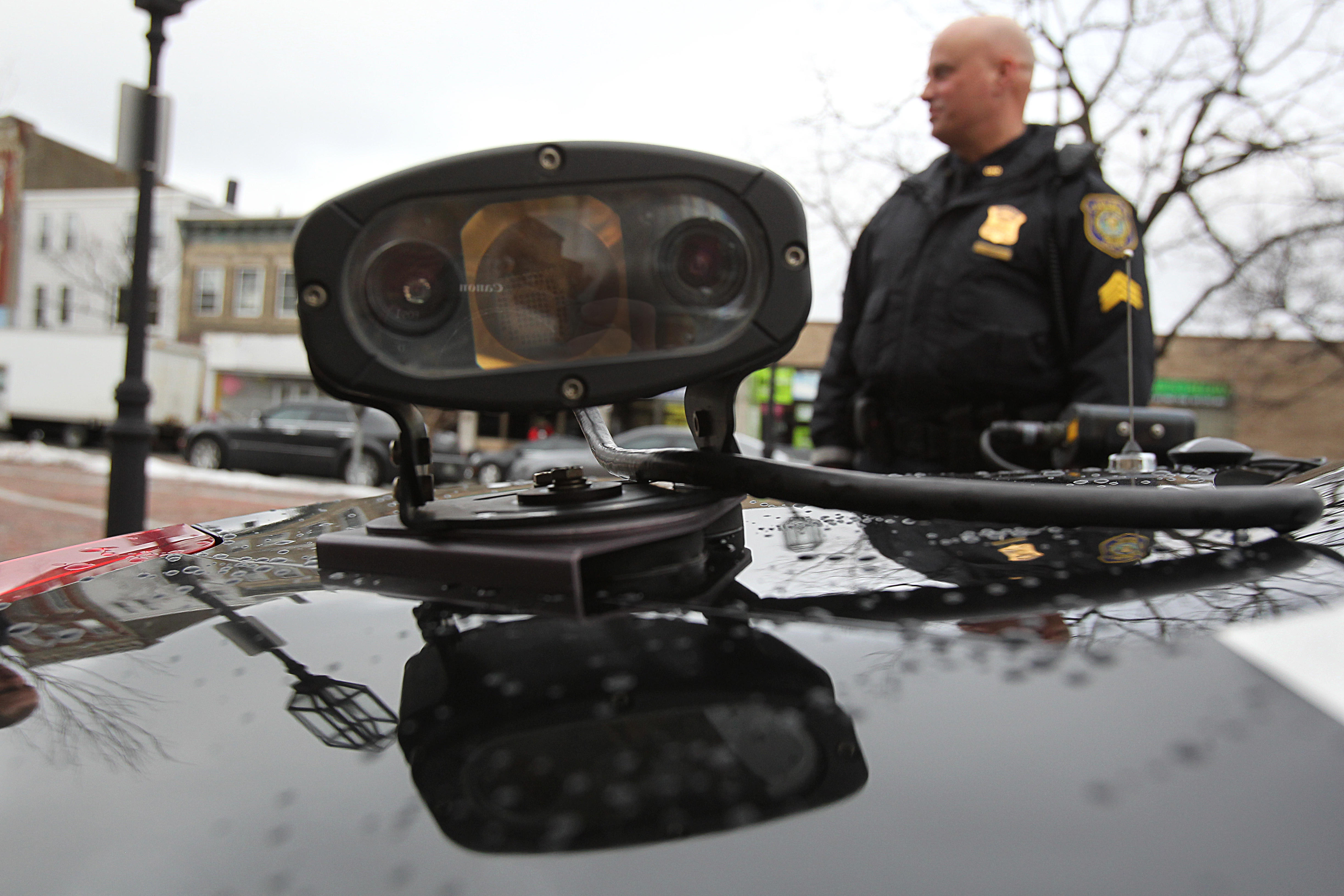 A police officer stands behind a cruiser that's mounted with an automated license plate reader.