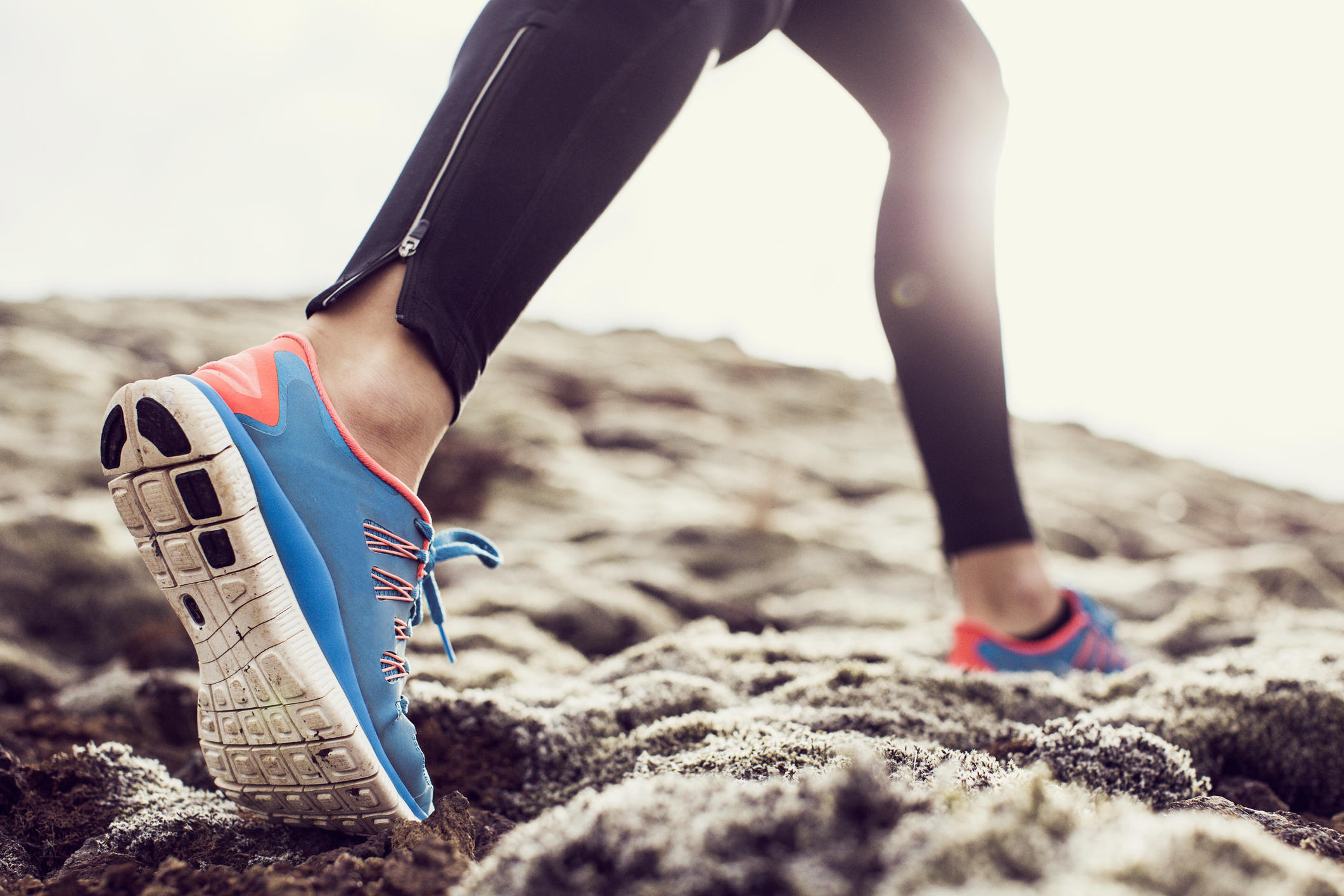 Close up of trainers running through mossy terrain