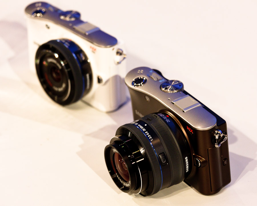 Two Samsung NX100 cameras, a white one with the 20mm f2.8 lens and a black one with the 20-50mm f3.5-5.6 lens. The camera will come in white, black, silver, and brown.