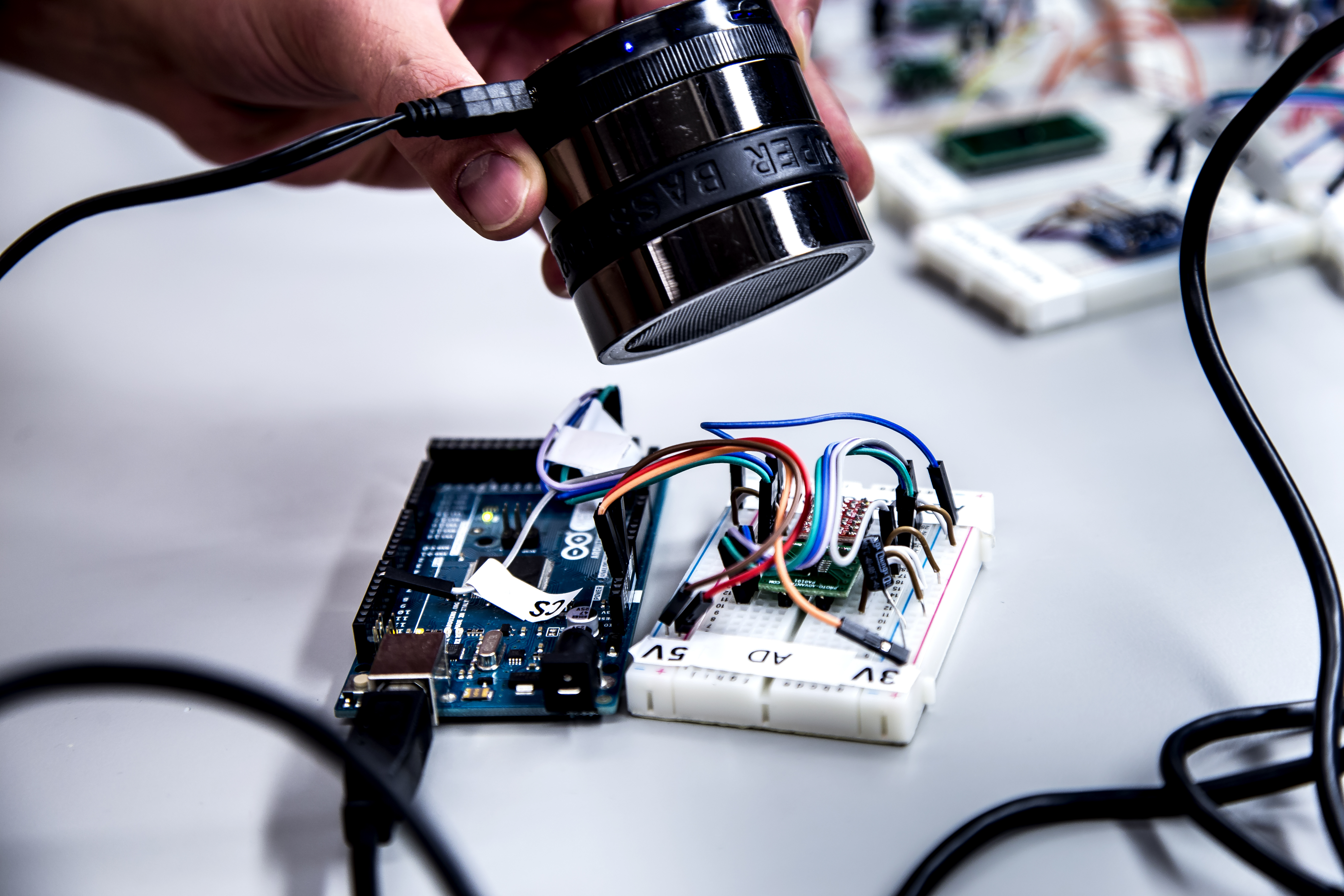 A University of Michigan researcher points a speaker at an accelerometer, which can send false readings to a phone, fitness tracker or other device.