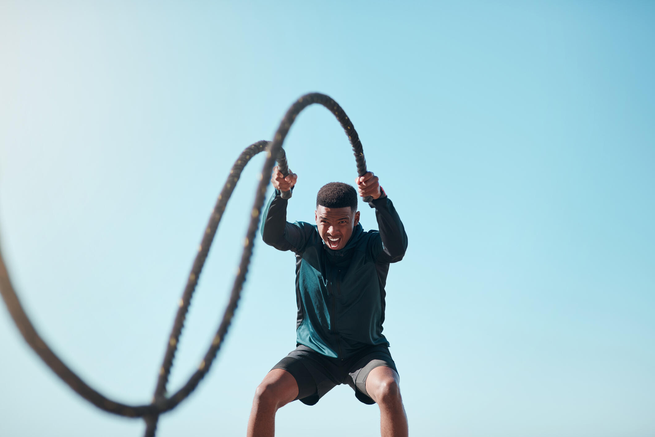 a young man doing high-intensity exercises with outdoor ropes