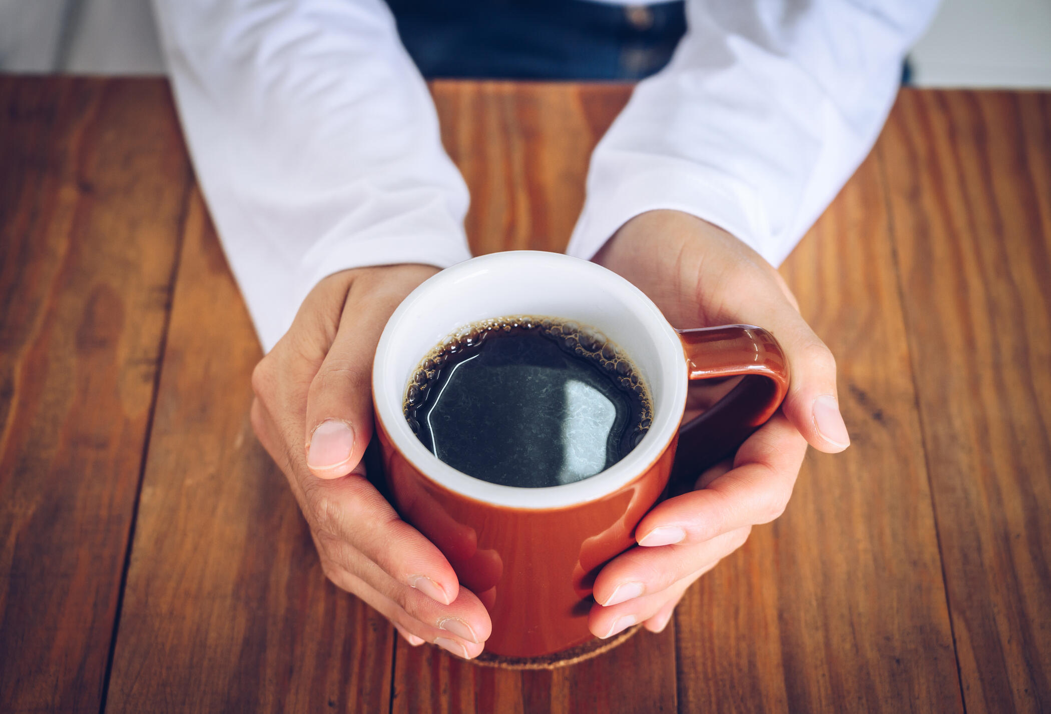 aerial view of a person holding a cup of black coffee with both hands