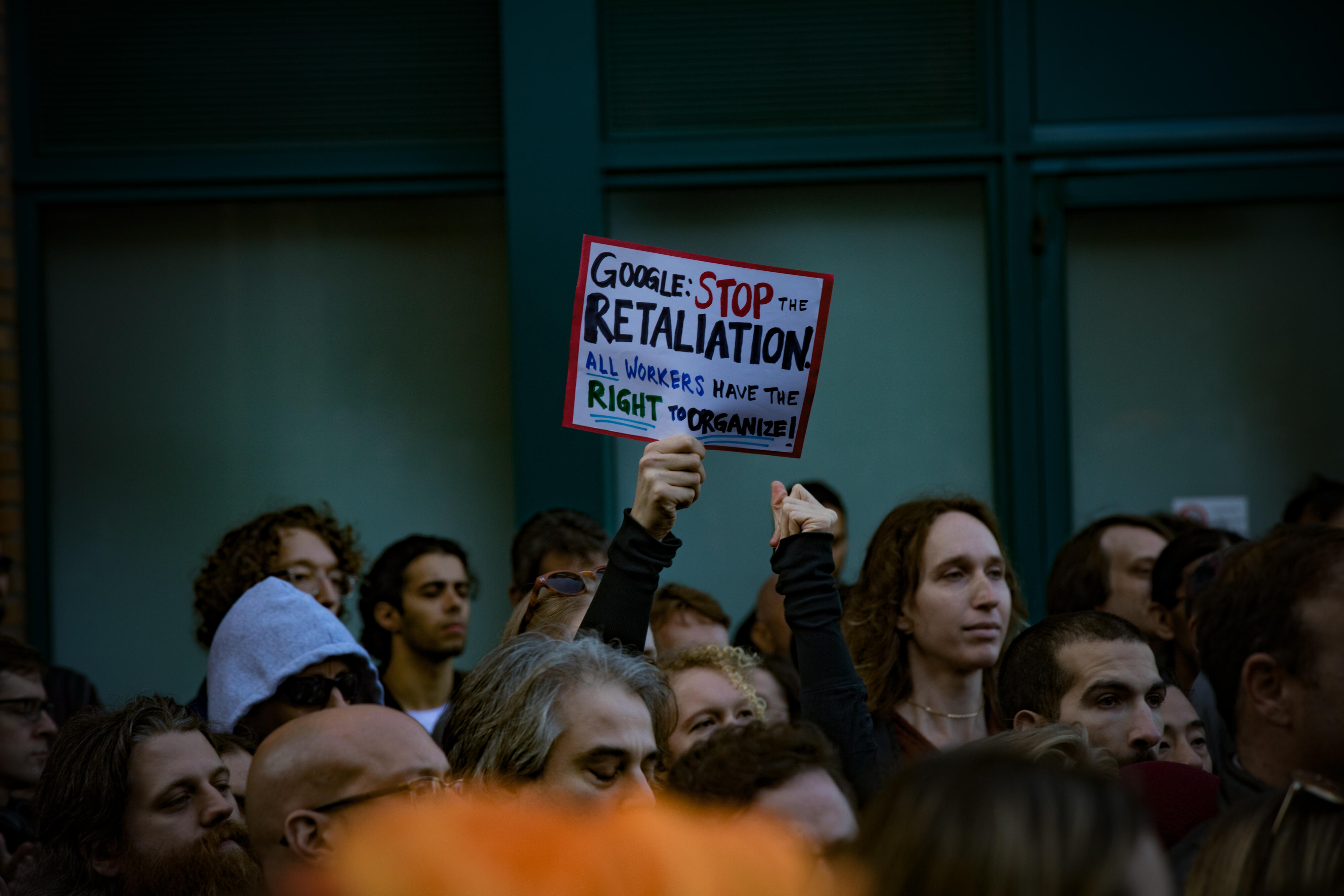"""Protesters with a sign: """"Google: Stop the retaliation. All workers have the right to organize!"""""""