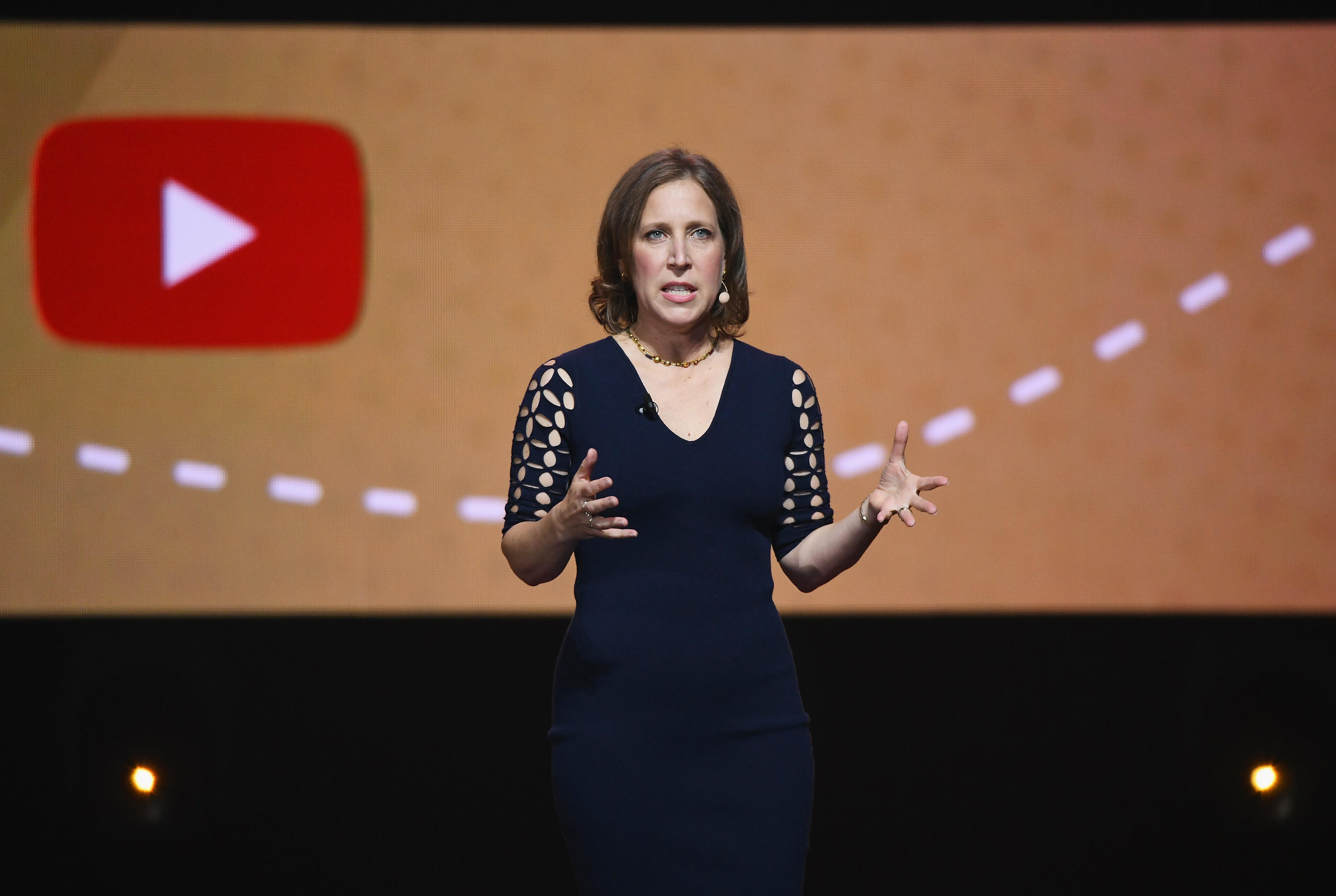 YouTube CEO Susan Wojcicky gestures on stage with the YouTube logo behind her