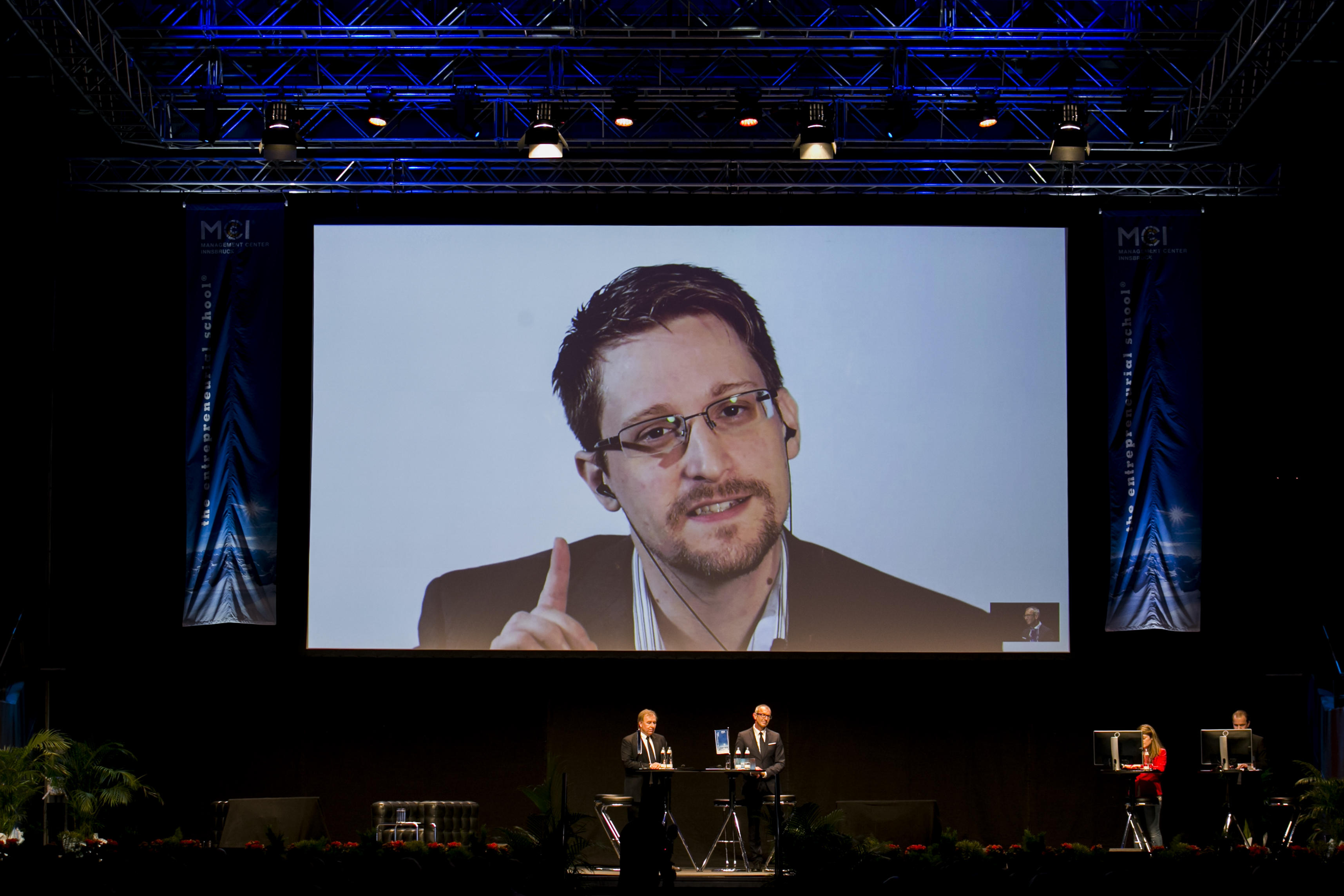 Video of Edward Snowden shown on a large screen above a stage.