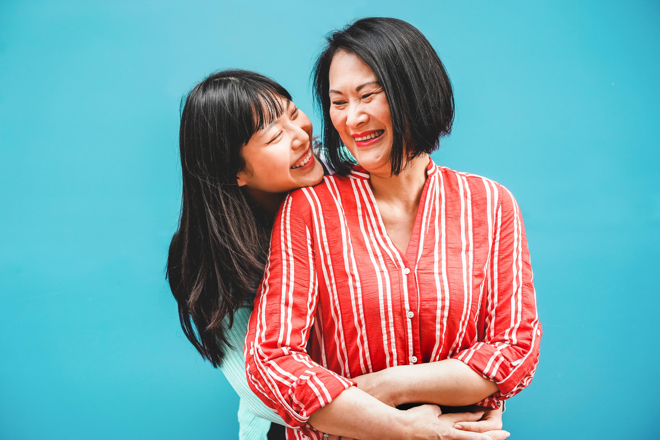 Asian mom and daughter hugging and smiling in front of a bright blue backdrop.