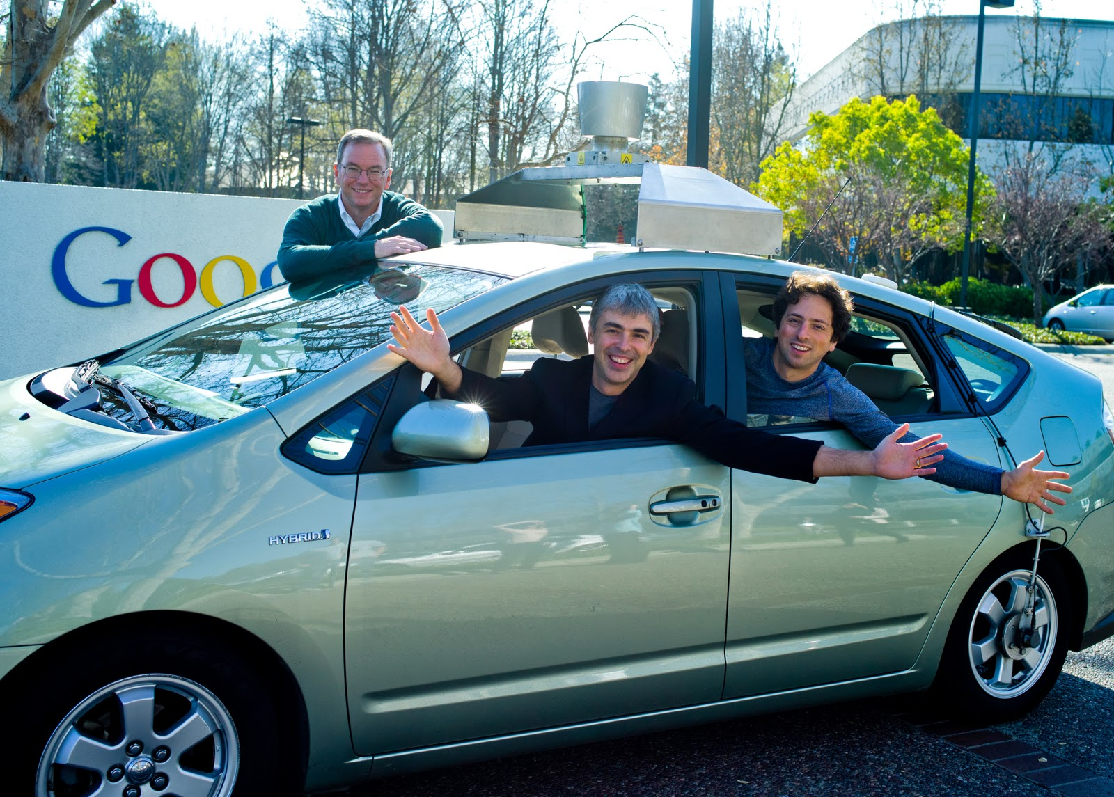 Google co-founders Larry Page, left, and Sergey Brin, inside a Google self-driving car, with Executive Chairman Eric Schmidt standing behind. The self-driving cars are reportedly part of Google X, a collection of advanced technology projects.