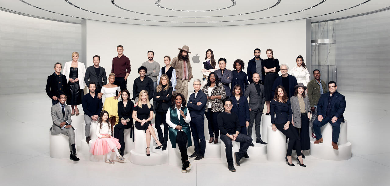 A group of more than 30 stars stand in a clean white Apple lobby