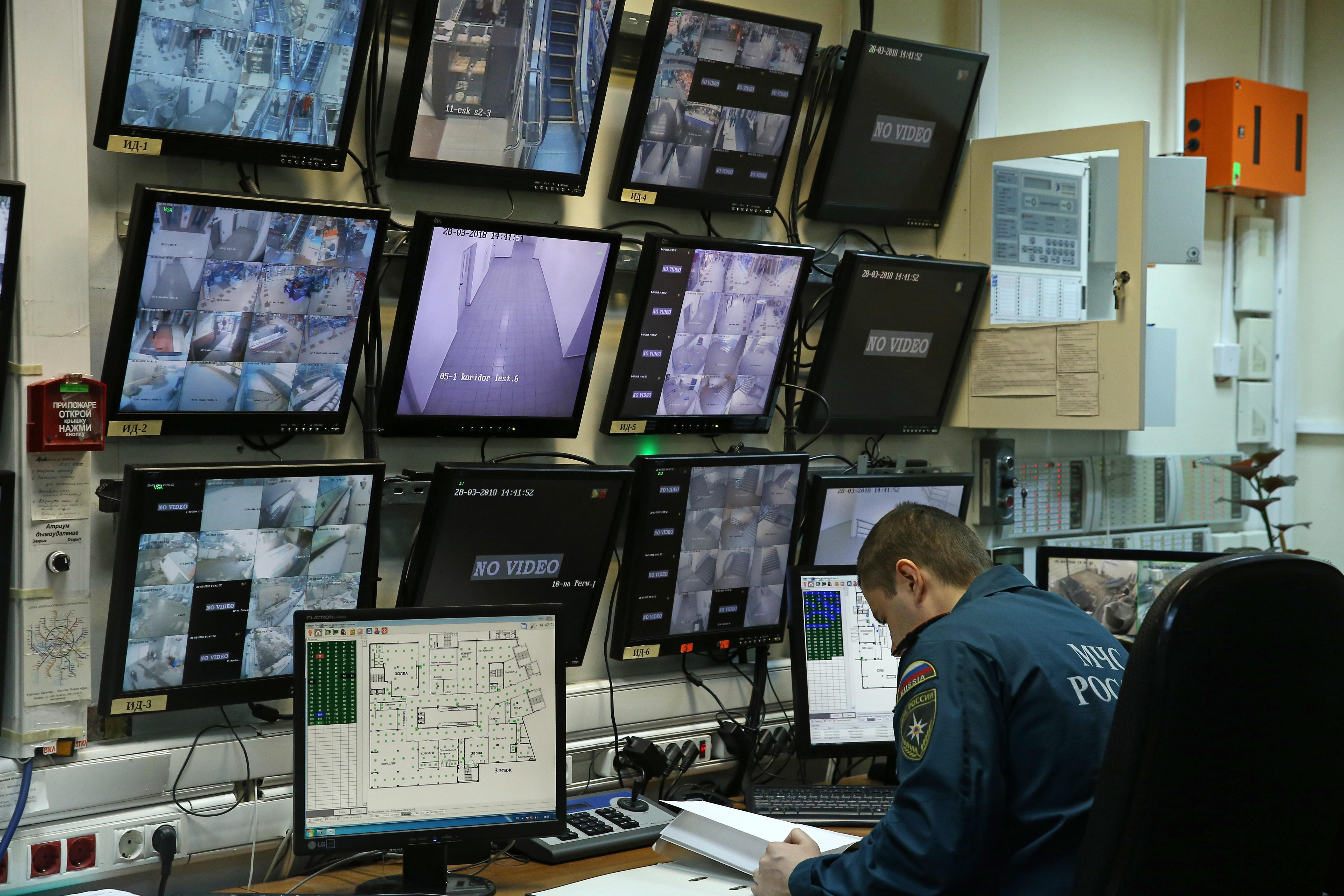 A security official sits in front of a bank of 12 camera monitors