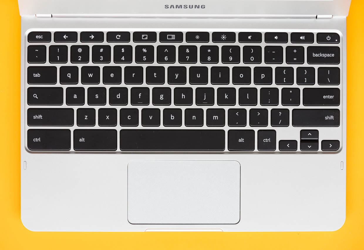 The Samsung Chromebook has a non-backlit chiclet keyboard with controls for screen brightness, volume, window switching, and browser navigation along the top. A wide trackpad supports multitouch gestures.