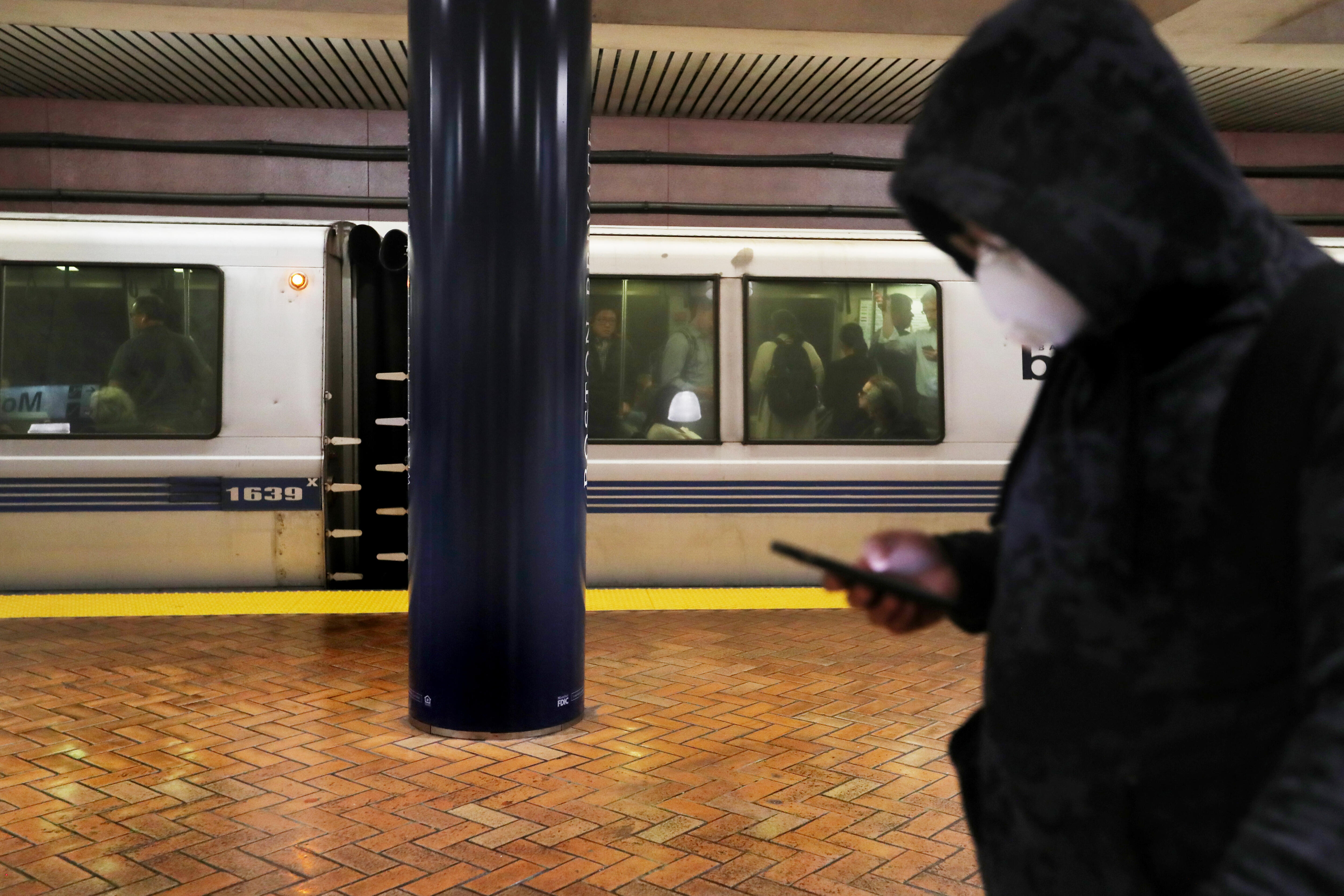 A commuter at a Bay Area Rapid Transit station wears a mask to protect against the coronavirus.