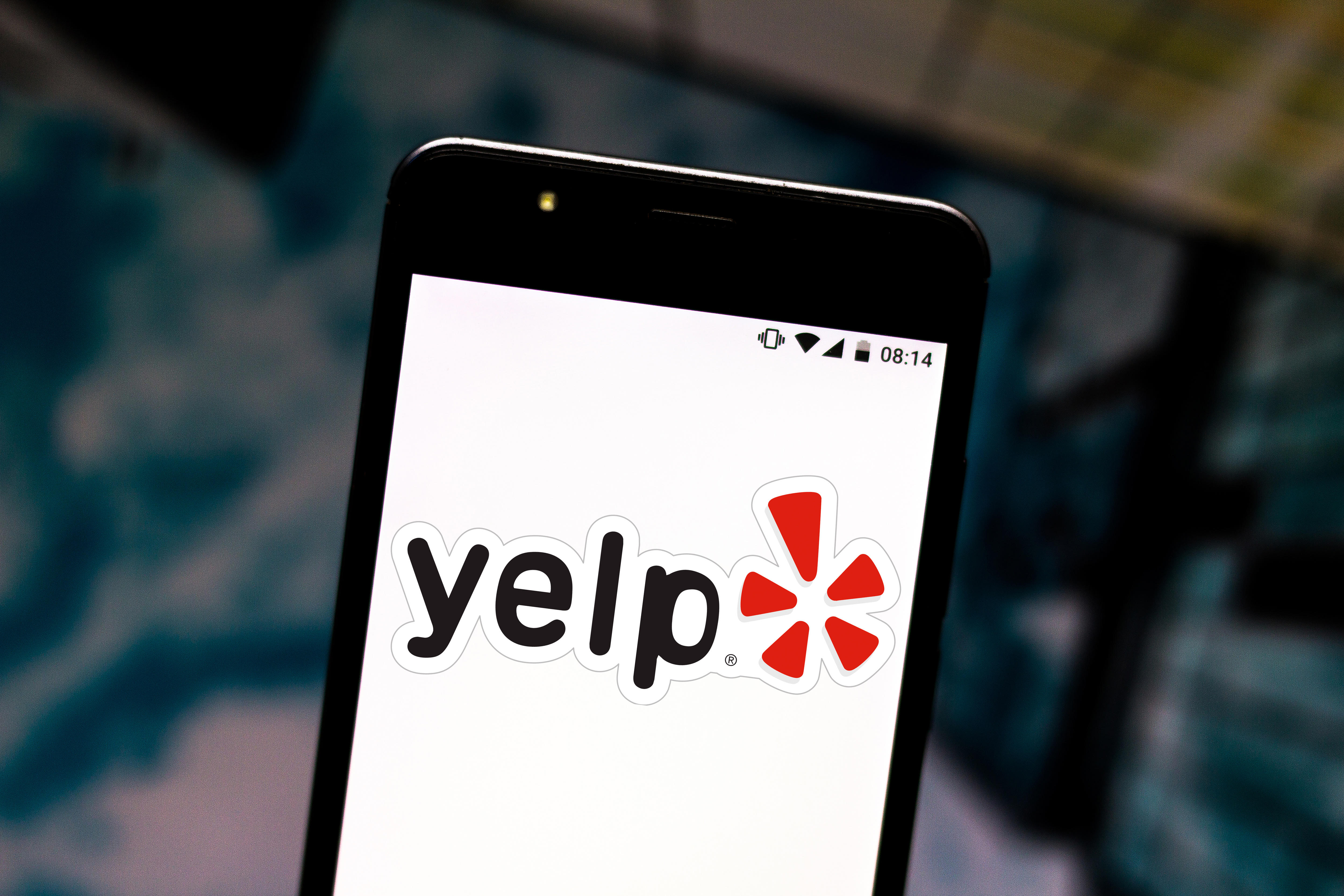 In this photo illustration the Yelp logo is seen displayed
