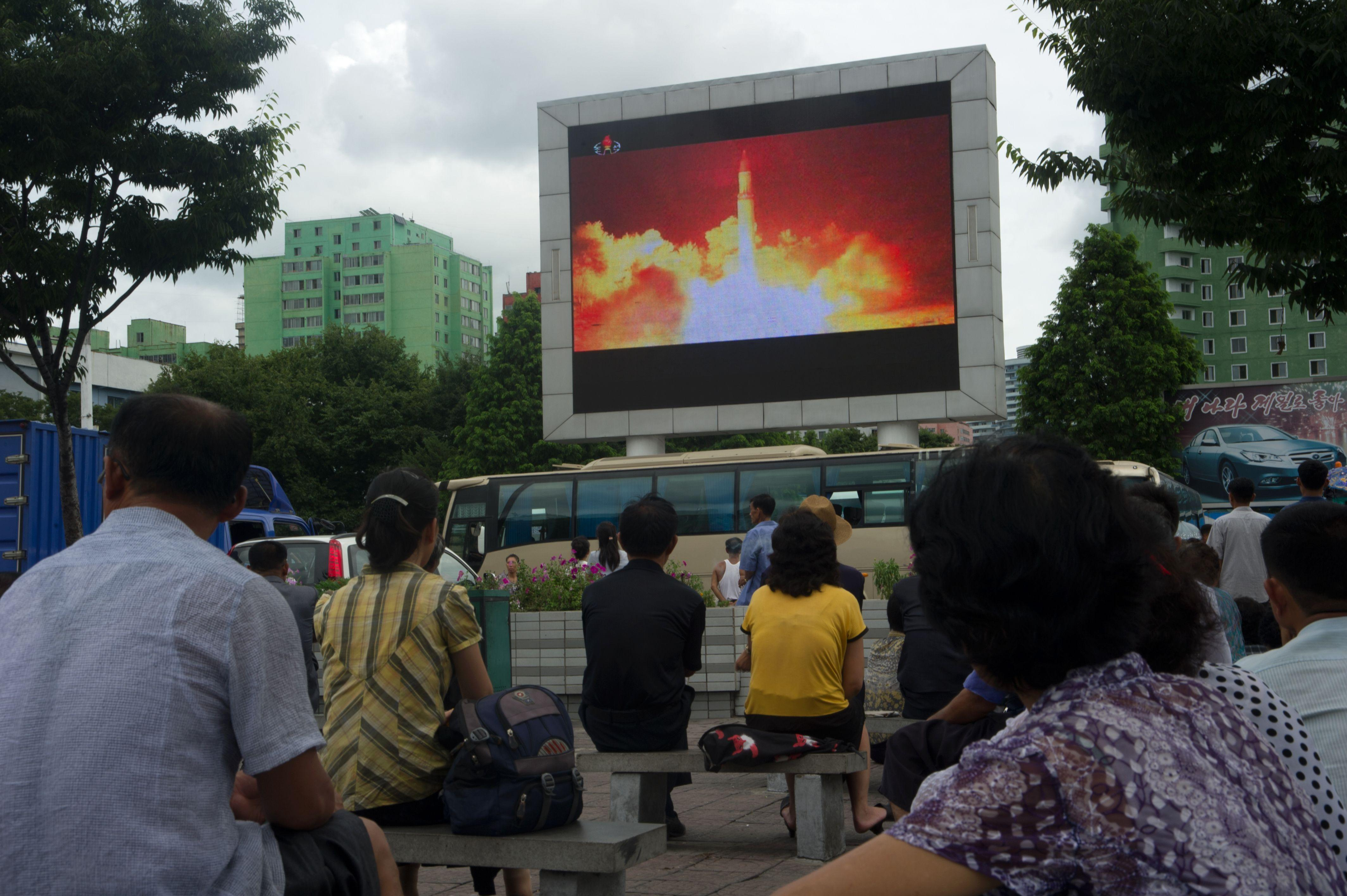 Missile launch shown on a large TV screen in a public square in Pyongyang, North Korea.