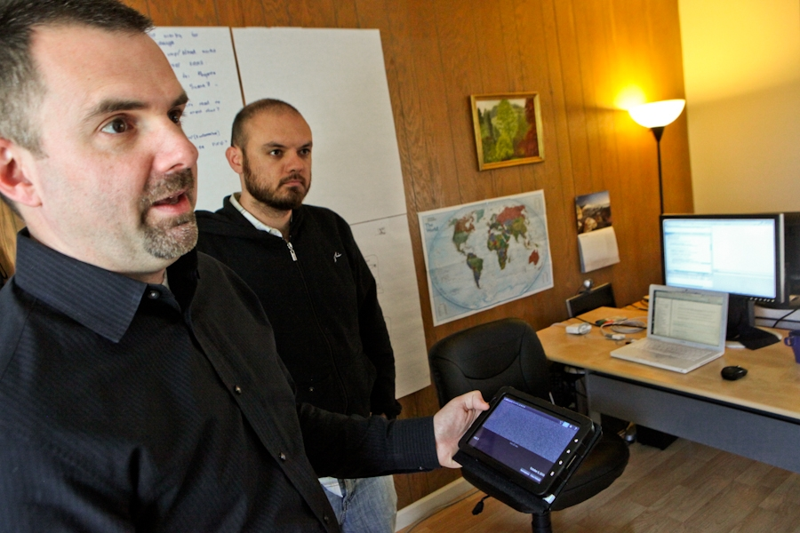 Francis Potter, founder and chief executive of The Hathersage Group, shows off the setiQuest Explorer mobile app he developed. Blake Barrett, application architect at the firm, (at right) helped him on the project.