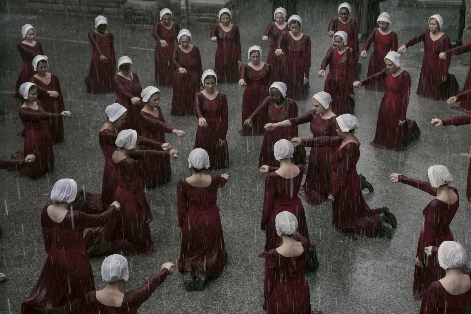 Handmaids gather in the rain in an episode of Hulu's The Handmaid's Tale