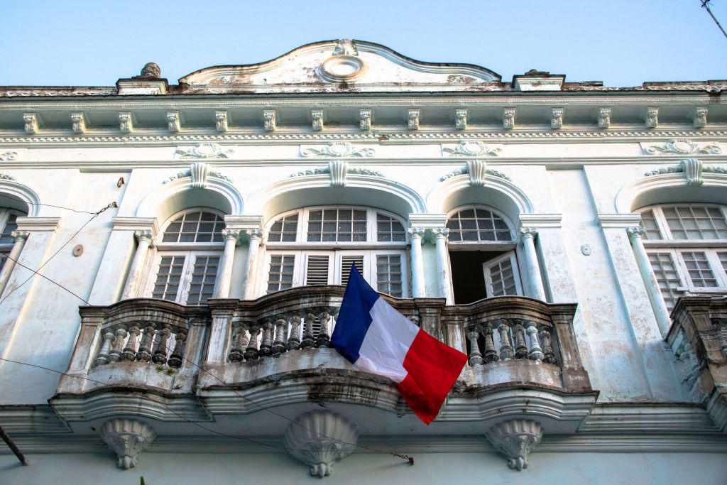 French flag hanging on an old house balcony during the