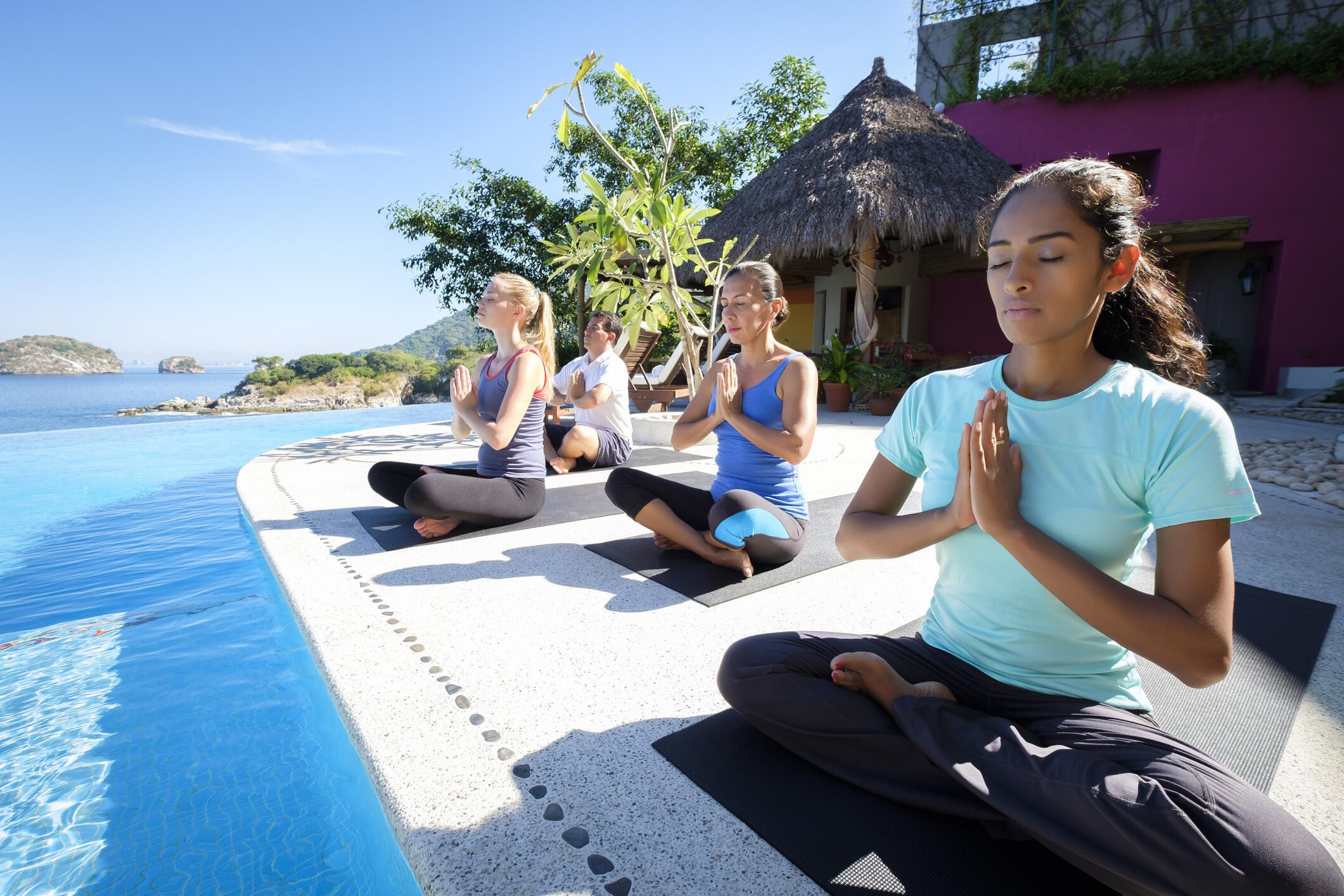 Group of people sitting on yoga mats on the edge of a pool in a tropical setting
