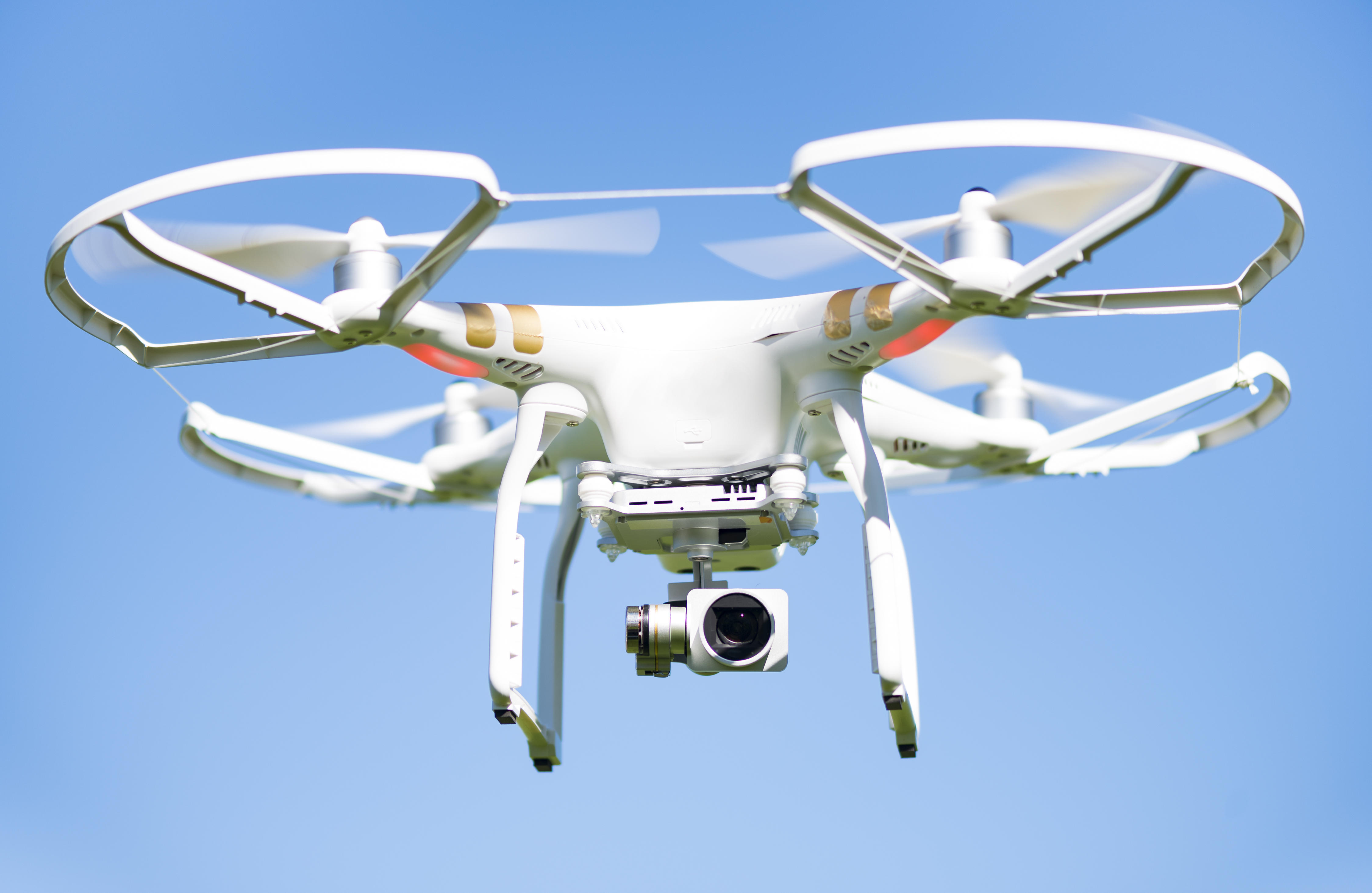 White drone flying high in the air, these unmanned aerial
