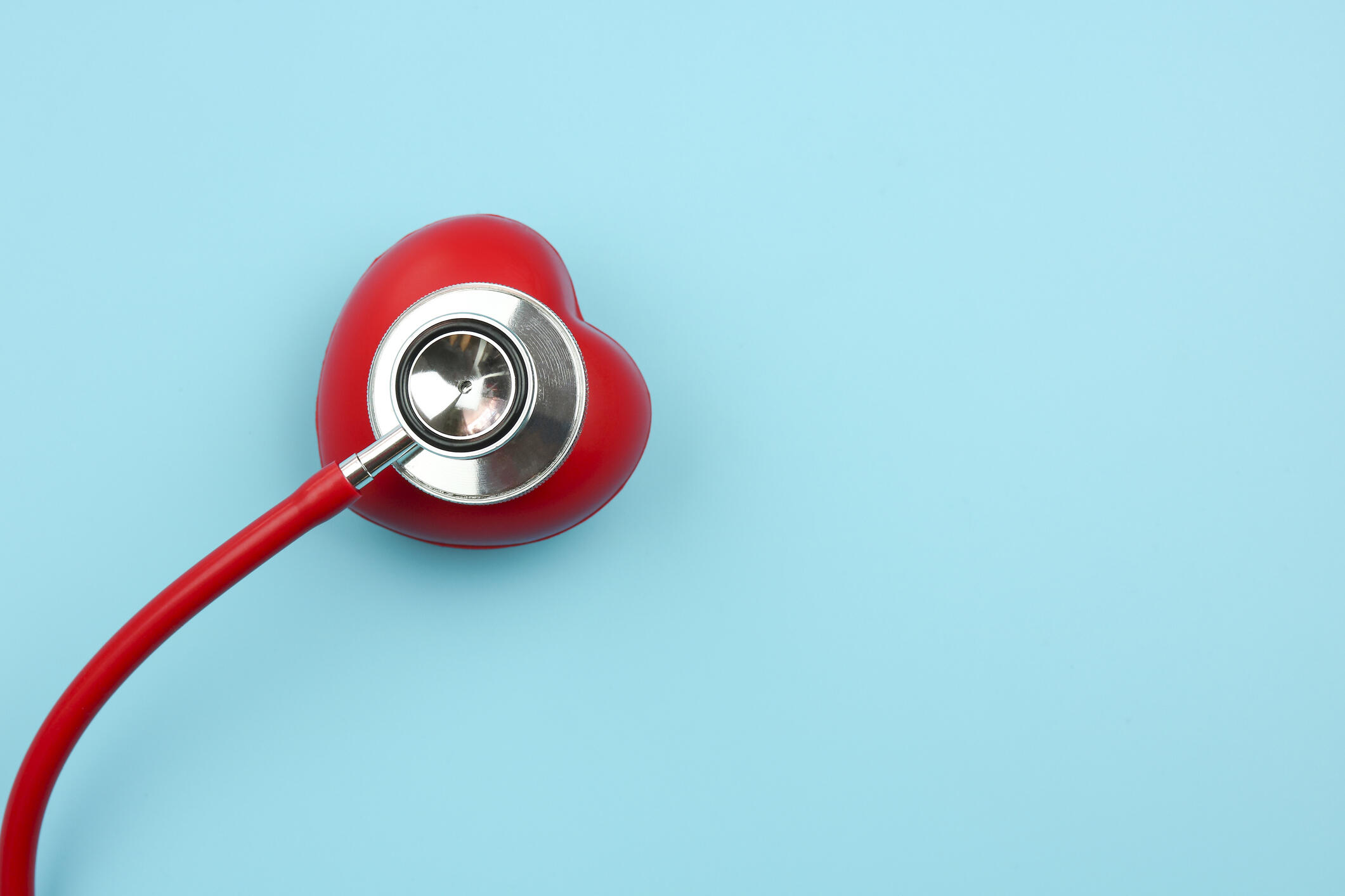 A red heart-shaped stethoscope on a teal background.