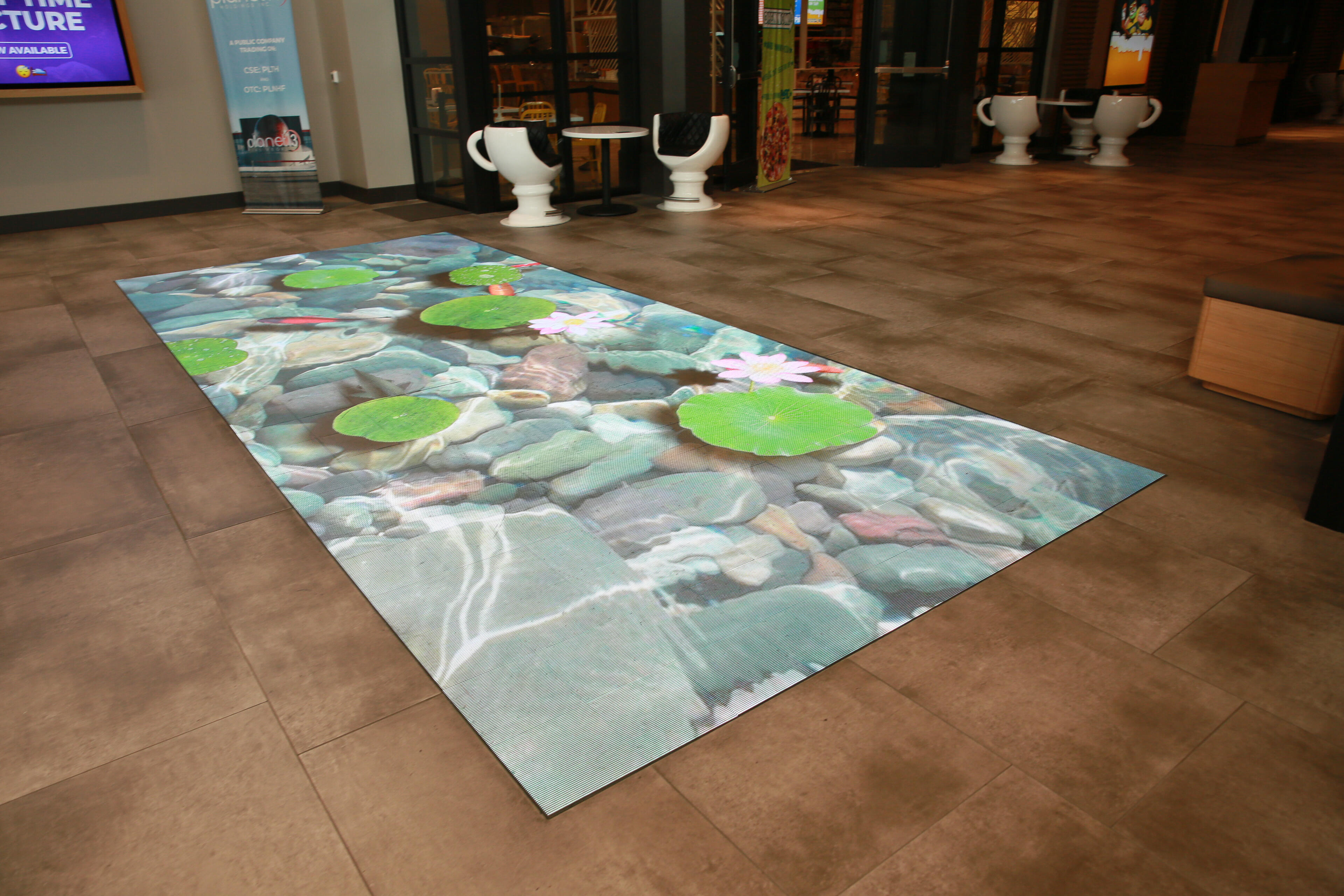Planet 13 loves showy tech! Check out this screen in the floor in the entryway, just past the check-in desks.