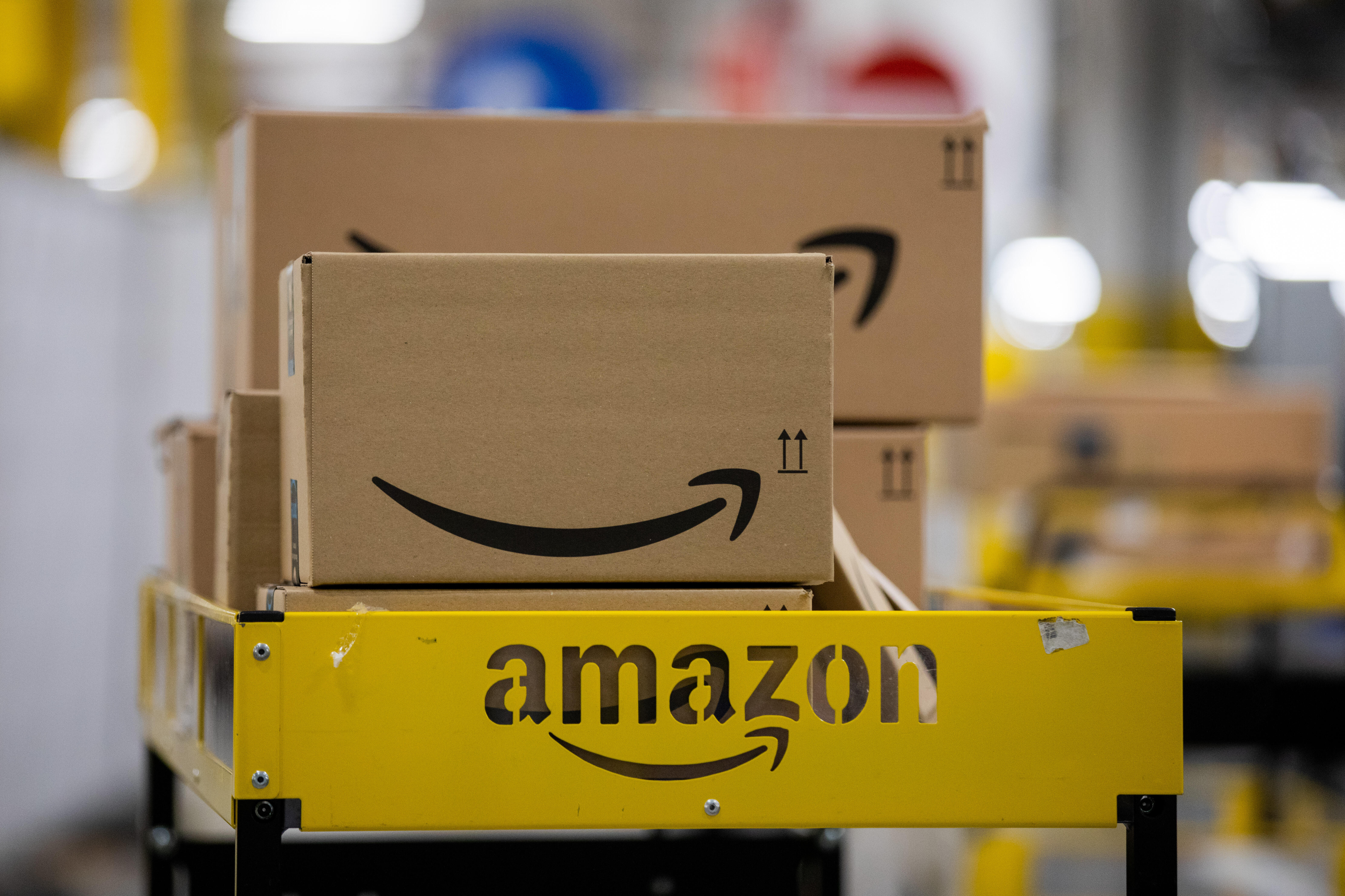 Brown boxes with Amazon's smiling logo on the side sit on a metal shelf.
