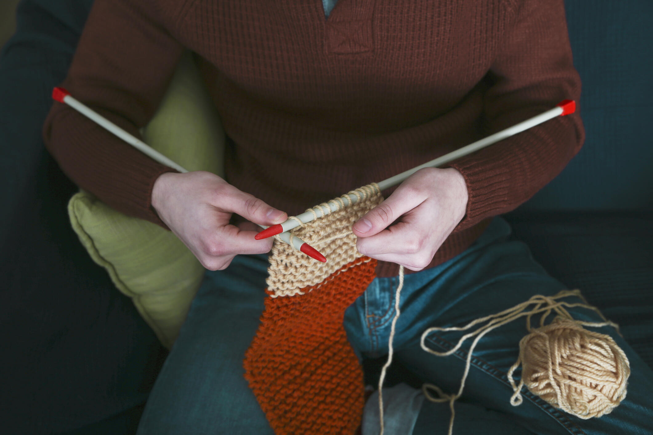 woman knitting red and cream-colored stocking for the holidays