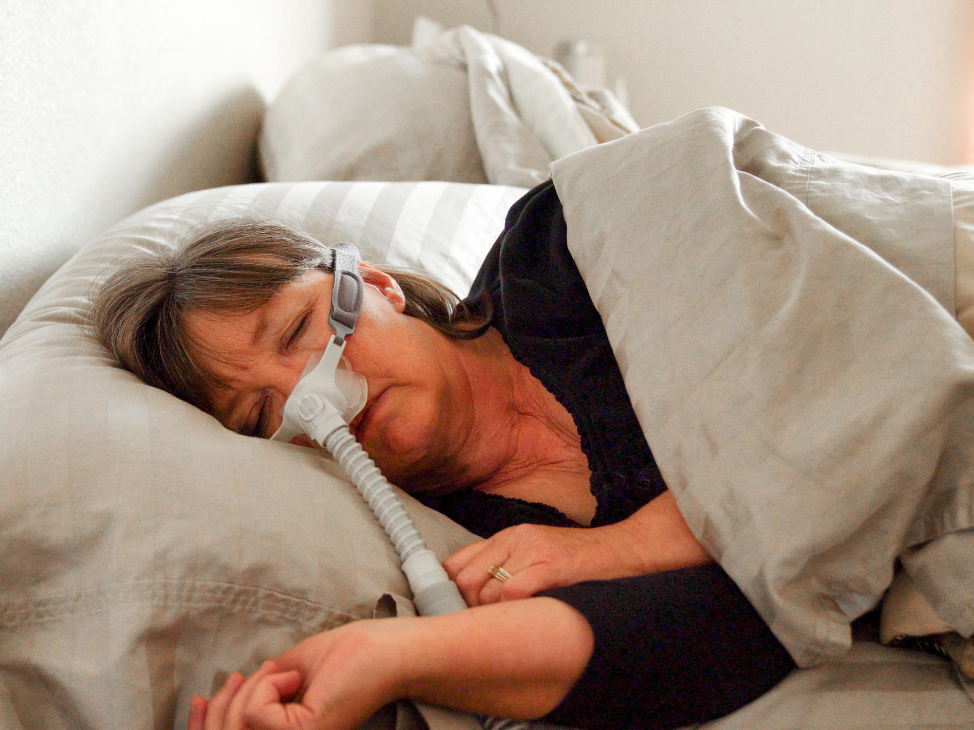 Middle Aged Woman With Sleep Apnea Asleep in a Bed Wearing a CPAP (Continuous positive airway pressure) machine to aid in her sleeping