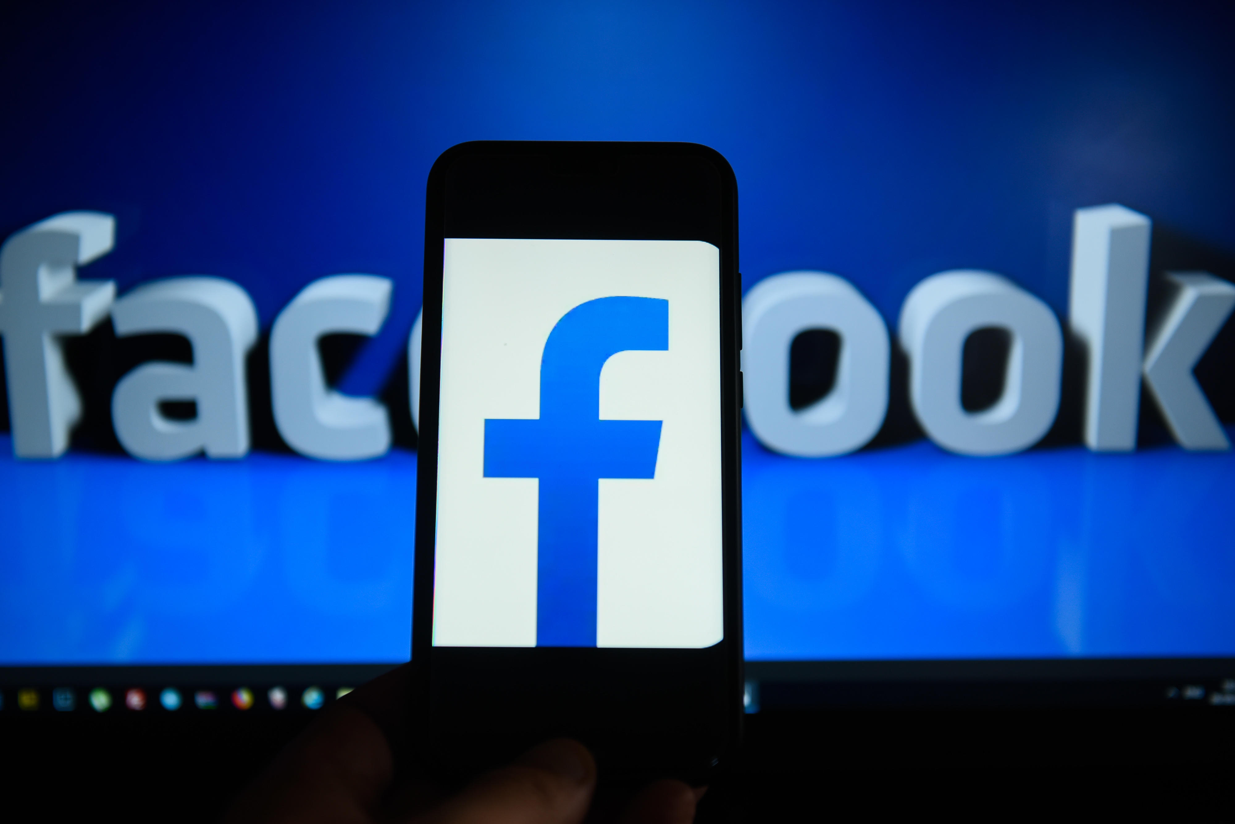 Facebook logo is seen on an android mobile phone in front