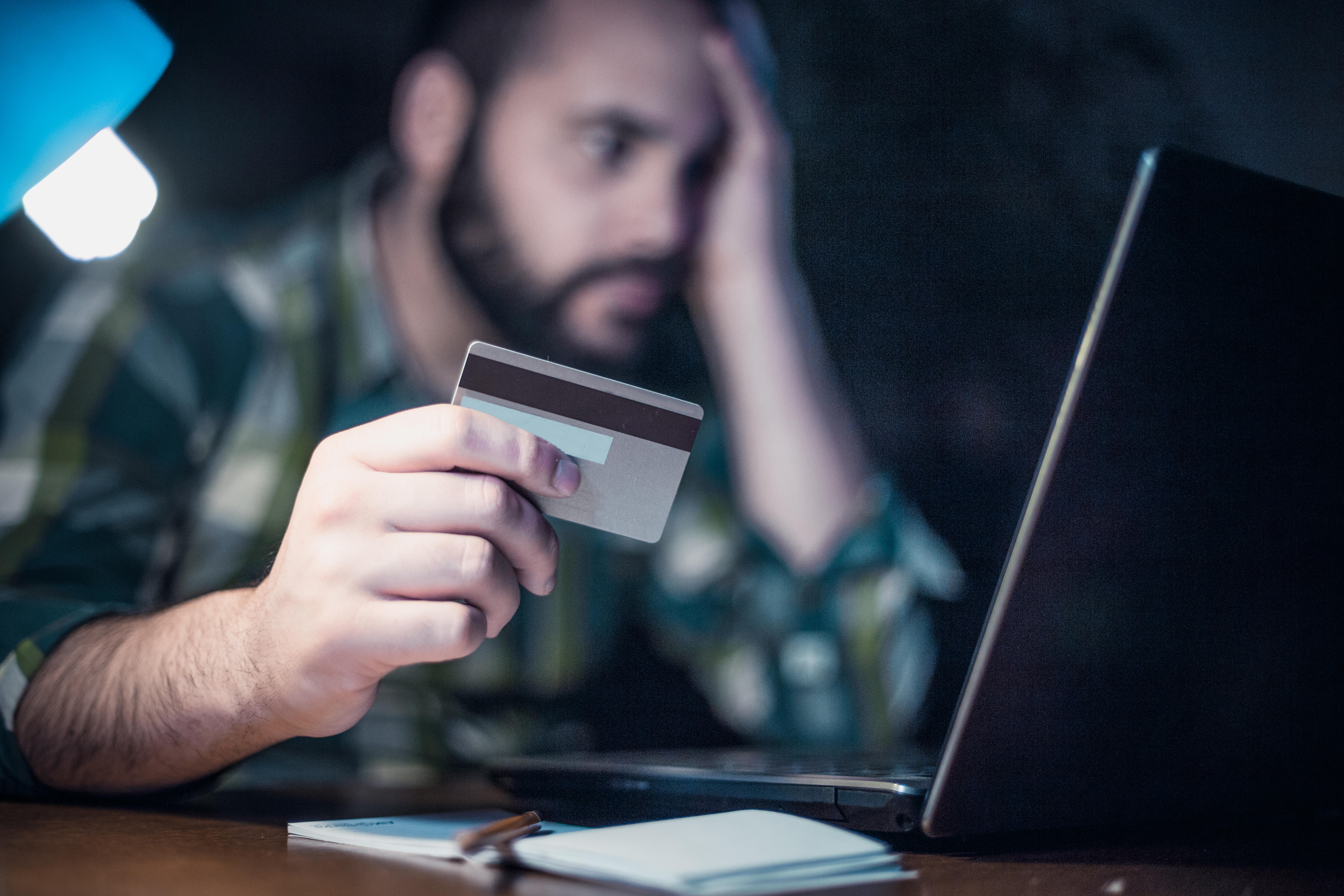 Man, with laptop, making a credit card payment