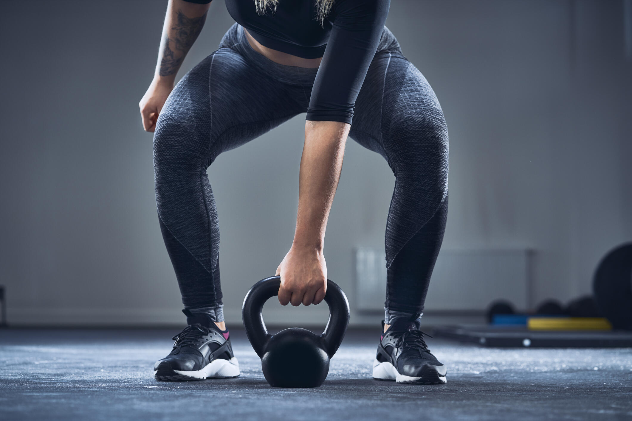 woman squatting with a kettlebell
