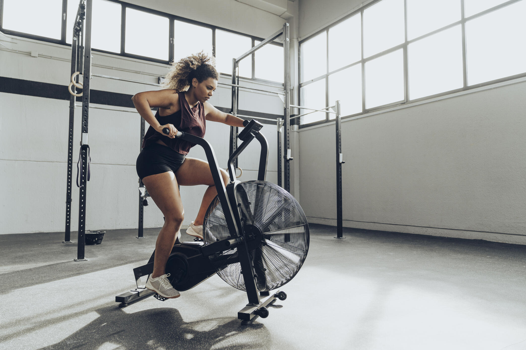 woman riding a stationary bike in a garage gym