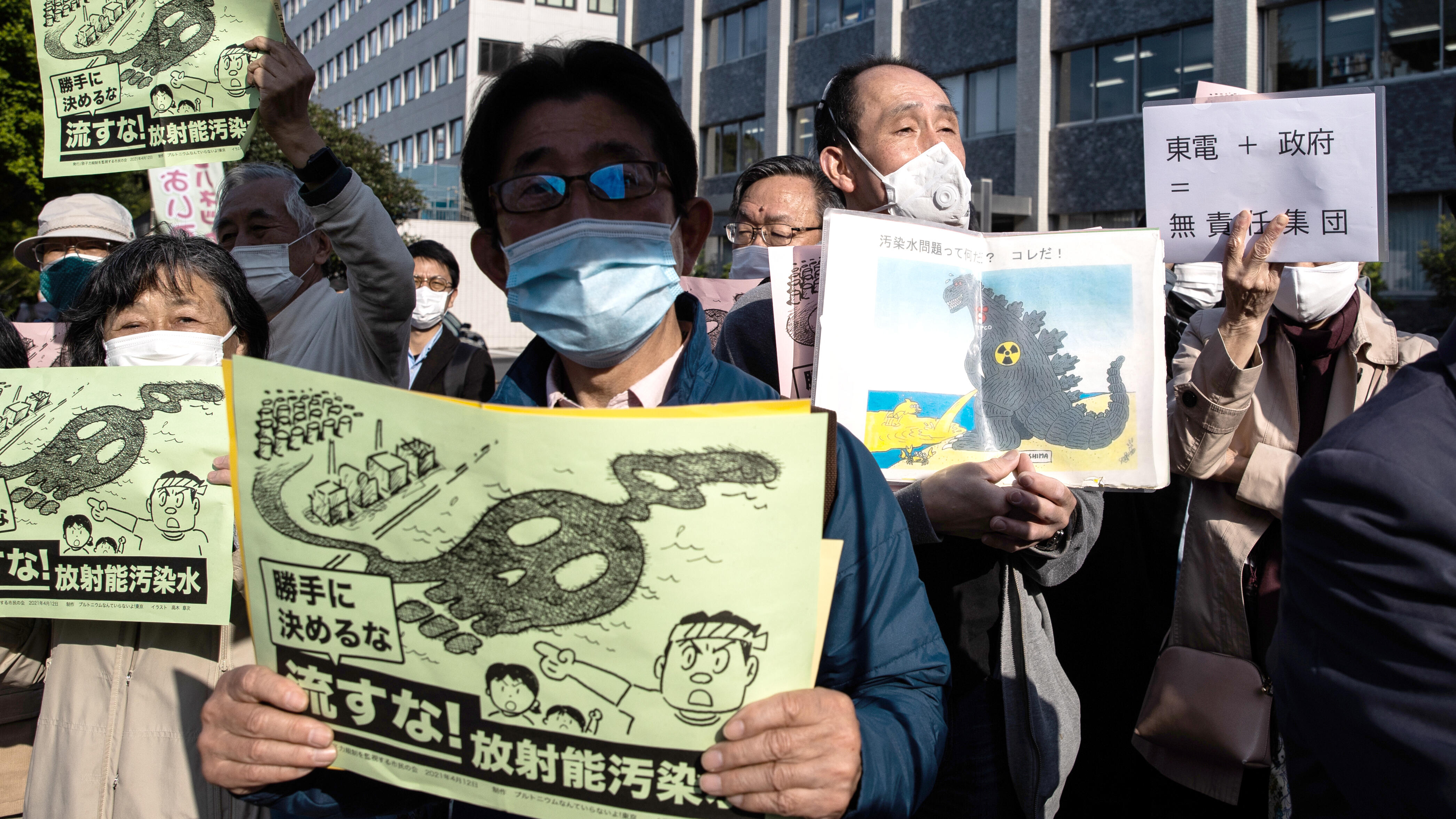 People with signs protesting Japan's plan to release contaminated water from Fukushima into the ocean