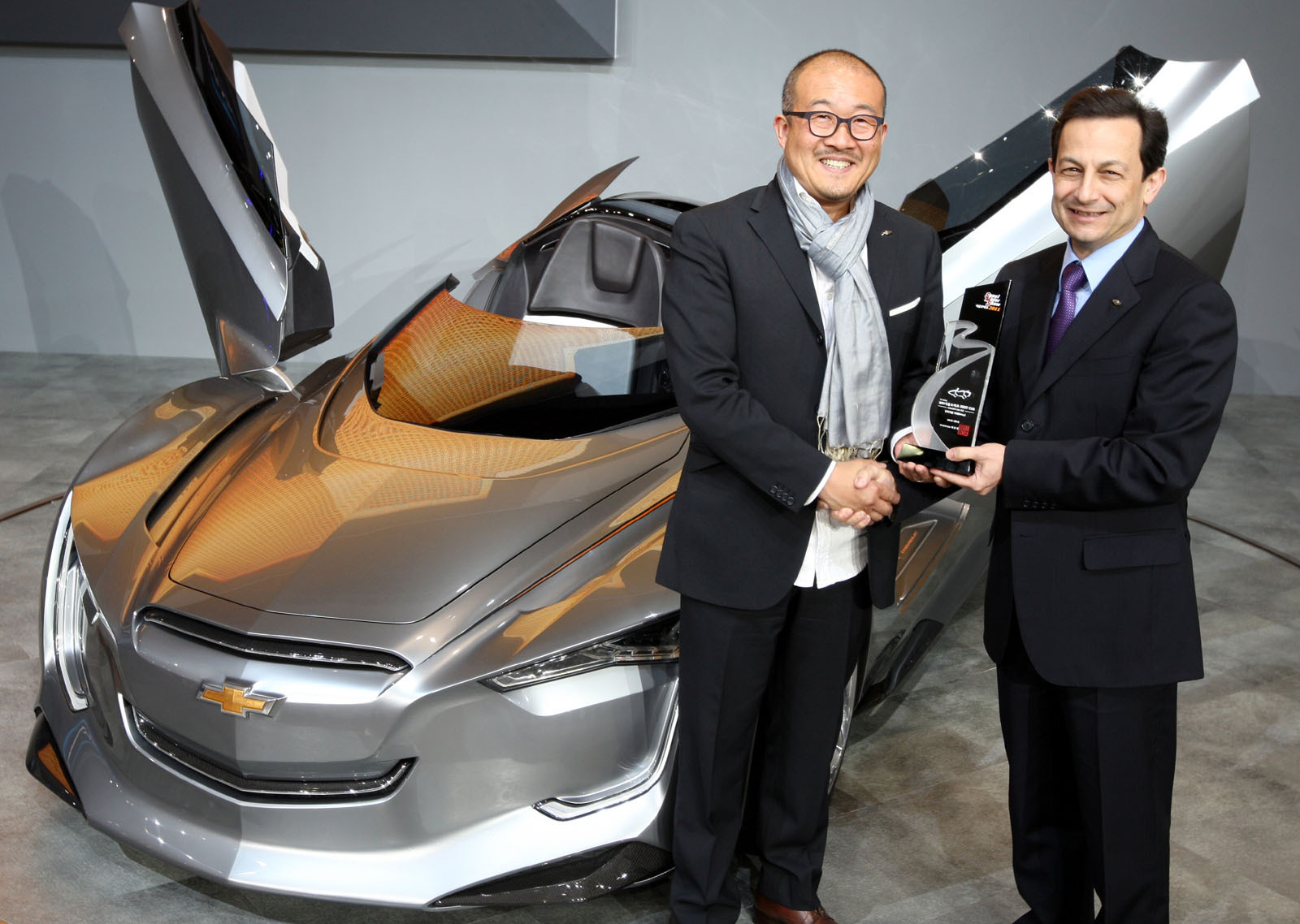 GM Director of Design Taewon Kim (left) and GM Korea President and CEO Mike Arcamone (right) holding the Best Concept Car award in front of the Mi-ray concept supercar at the 2011 Seoul Motor Show.