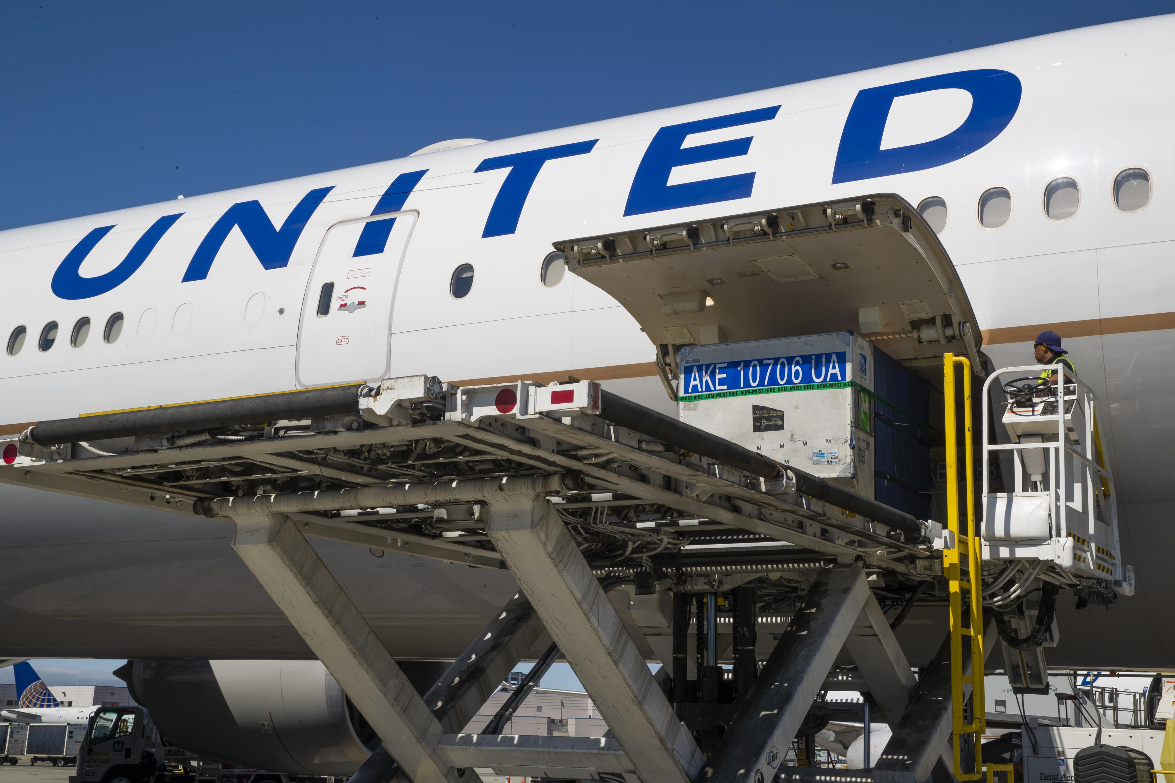Baggage containers get loaded into a United Airlines Boeing 777.