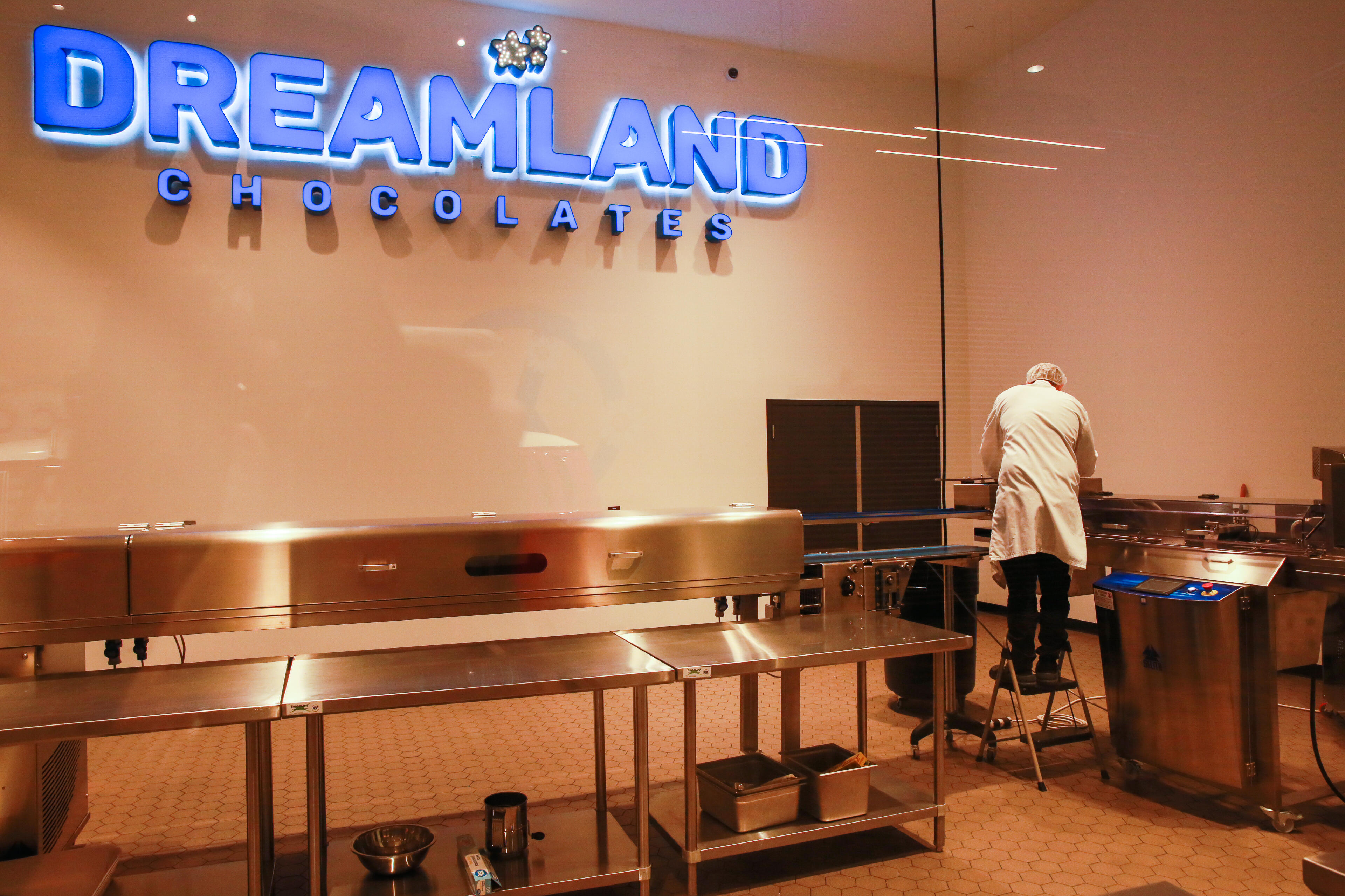 """When the Dreamland brand sign is blinking, that means chocolates are coming out on the conveyor belt. Reminds me of Krispy Kreme's """"Hot Fresh"""" signs!"""