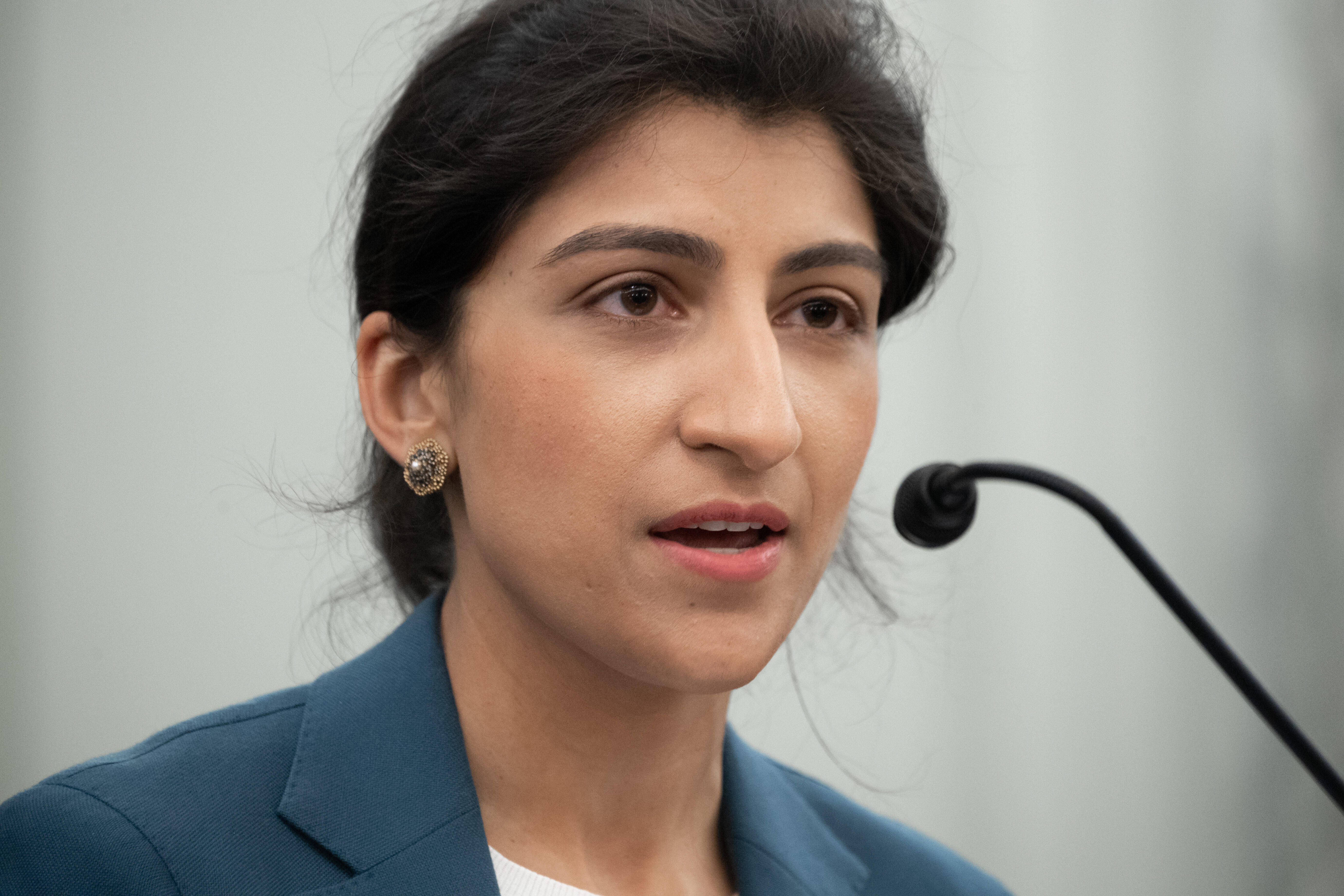Close up of Lina Khan speaking into a small microphone.