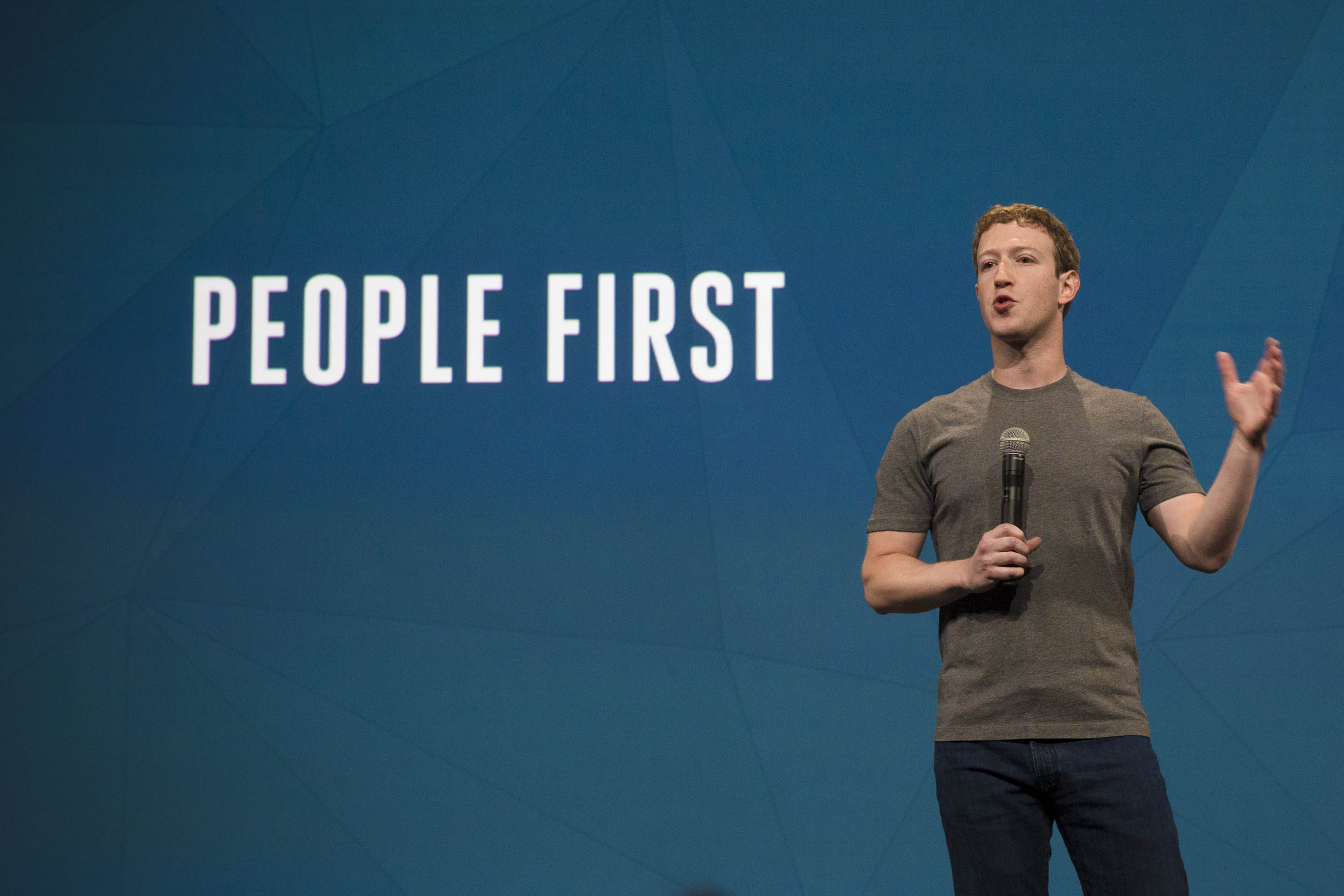 """Facebook CEO Mark Zuckerberg in front of a projection reading """"People First"""""""