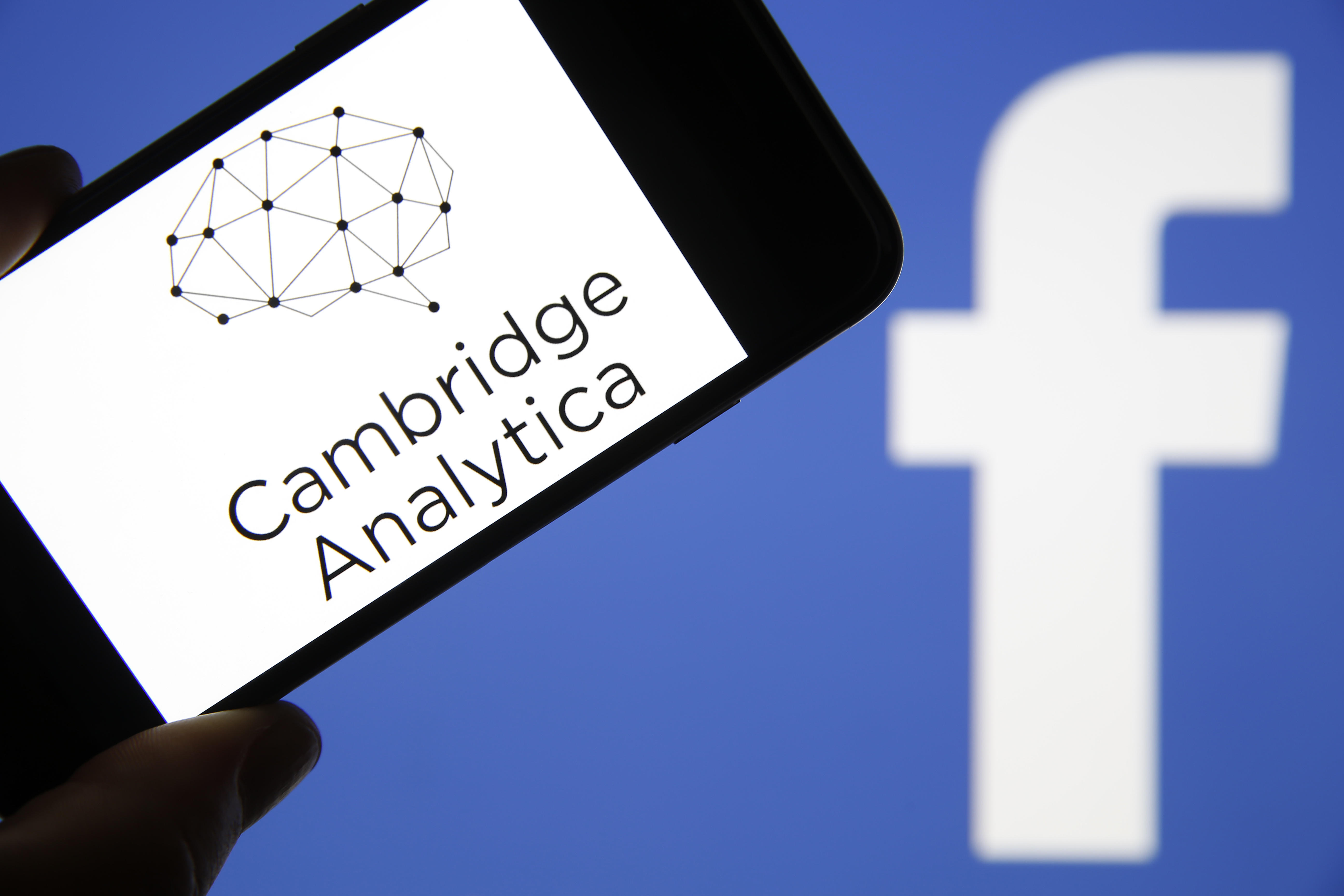 Cambridge Analytica name and logo on a smartphone screen, in front of the Facebook logo.