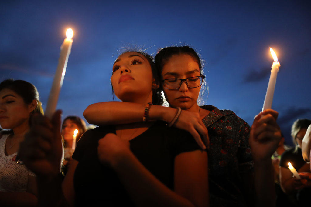 People attend a candlelight vigil at a makeshift memorial honoring victims of the mass shooting in El Paso, Texas.