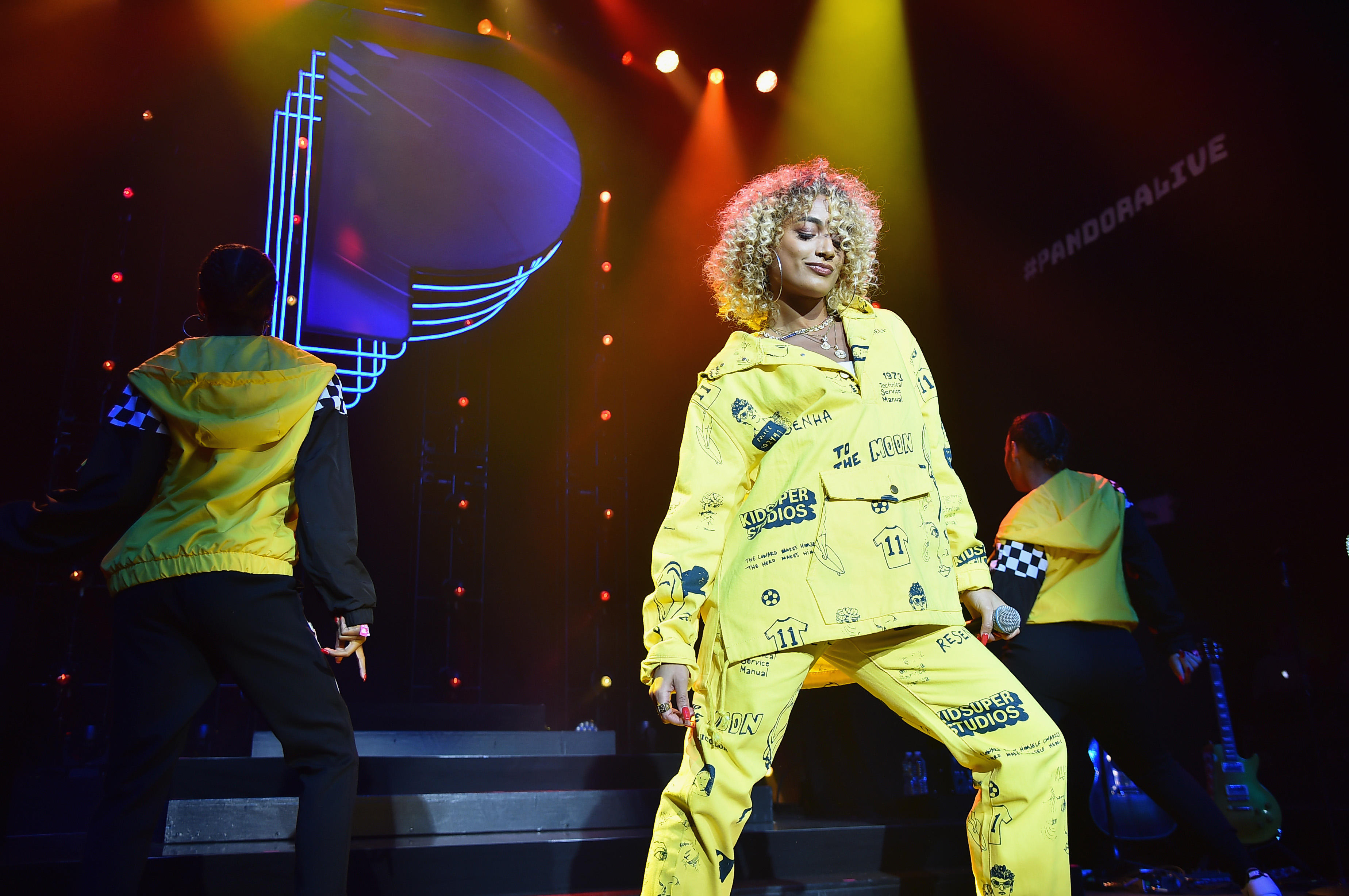 DaniLeigh performs in a yellow graphic outfit in front of a Pandora P logo.