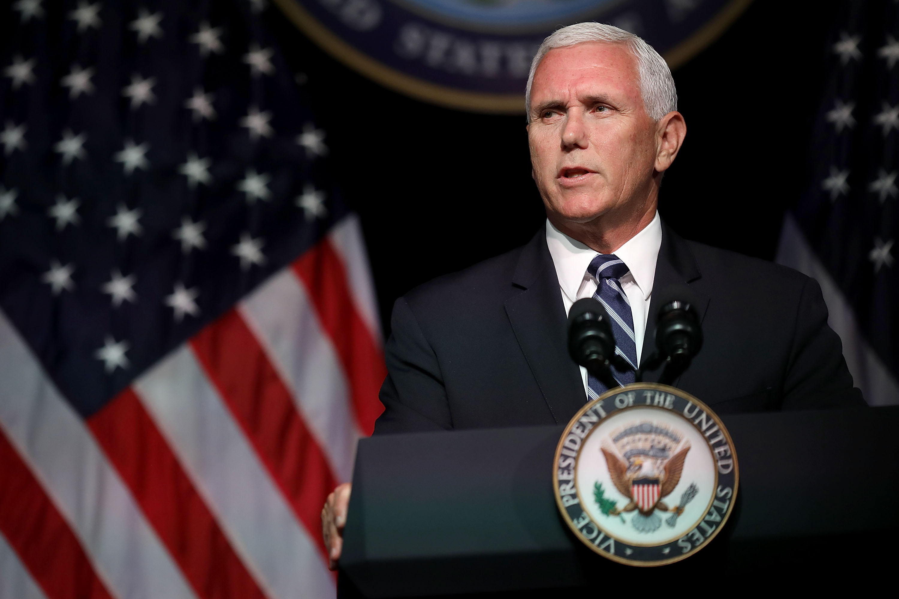 US Vice President Mike Pence giving a speech from a lectern that features the seal of the president. An American flag is visible in the background.